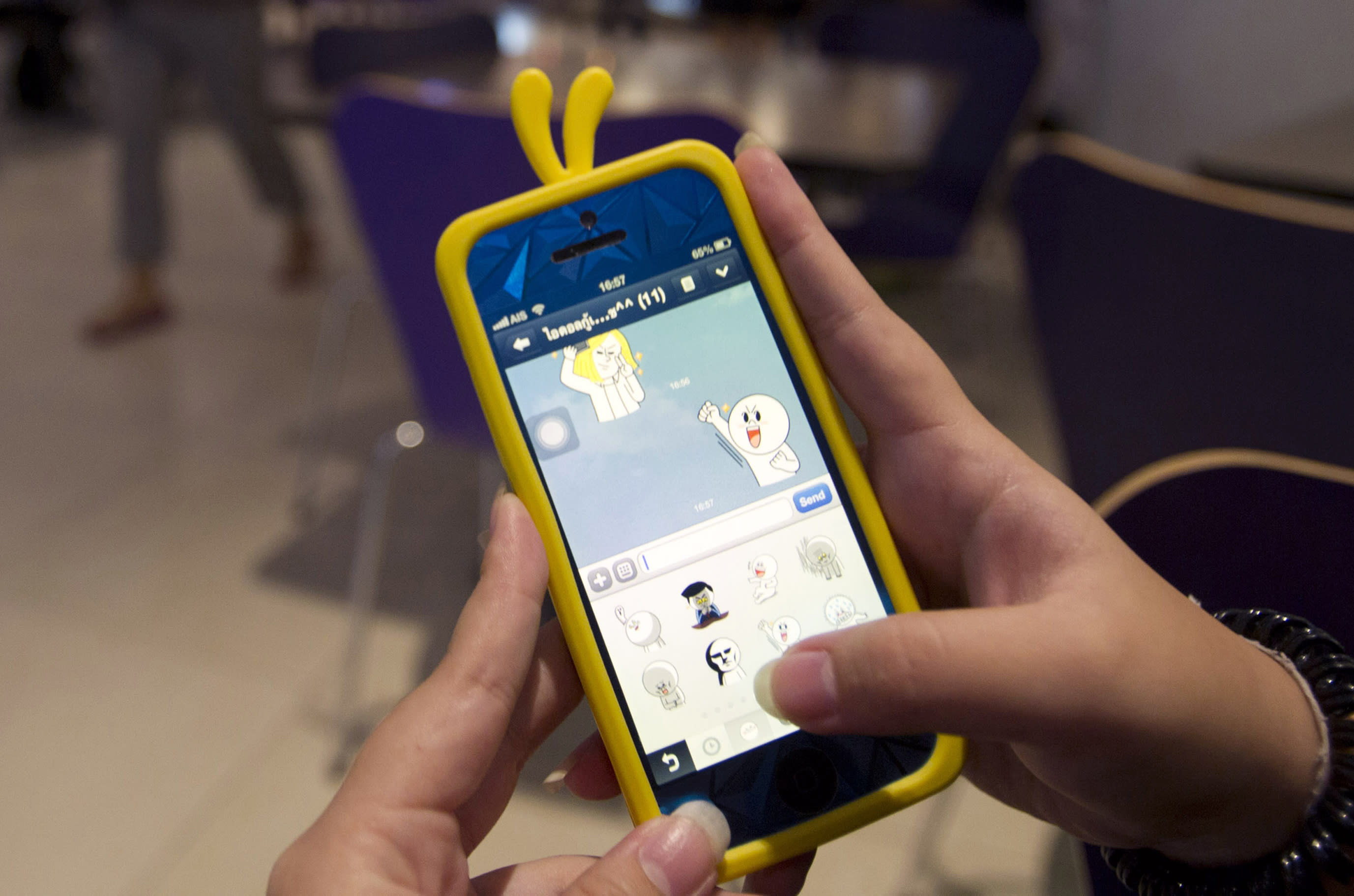 """A Thai teenager uses the """"Line"""" instant messaging app on her smartphone Tuesday, Aug. 13, 2013 in Bangkok, Thailand. Thai police asked the operator of the popular app for access to records of online chats, raising concerns about intrusive surveillance despite promising only suspected criminals would be targeted. (AP Photo/Sakchai Lalit)"""
