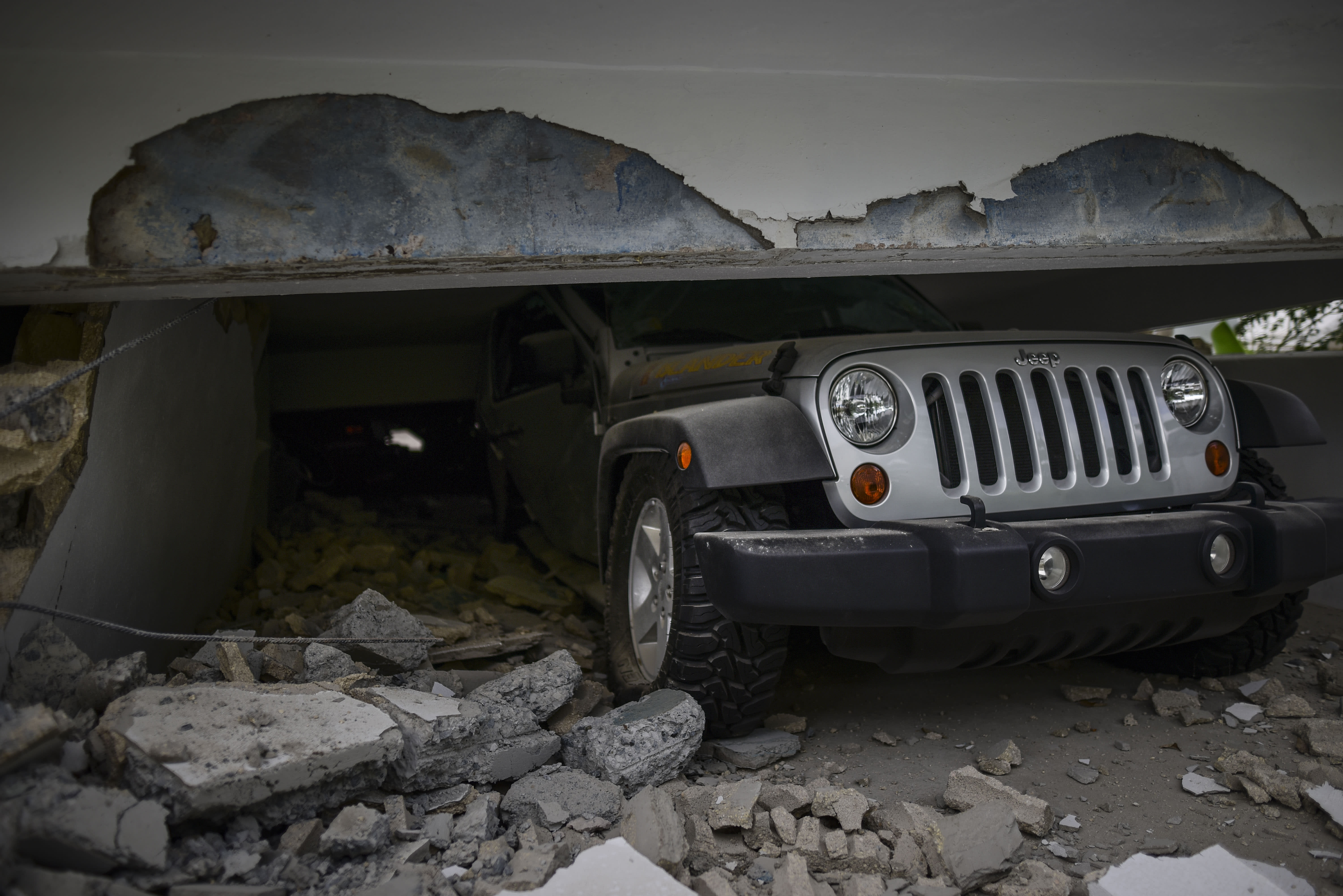 A car is crushed under a home that collapsed after the previous day's magnitude 6.4 earthquake in Yauco, Puerto Rico, Wednesday, Jan. 8, 2020. More than 250,000 Puerto Ricans remained without water on Wednesday and another half a million without power, which also affected telecommunications. (AP Photo/Carlos Giusti)