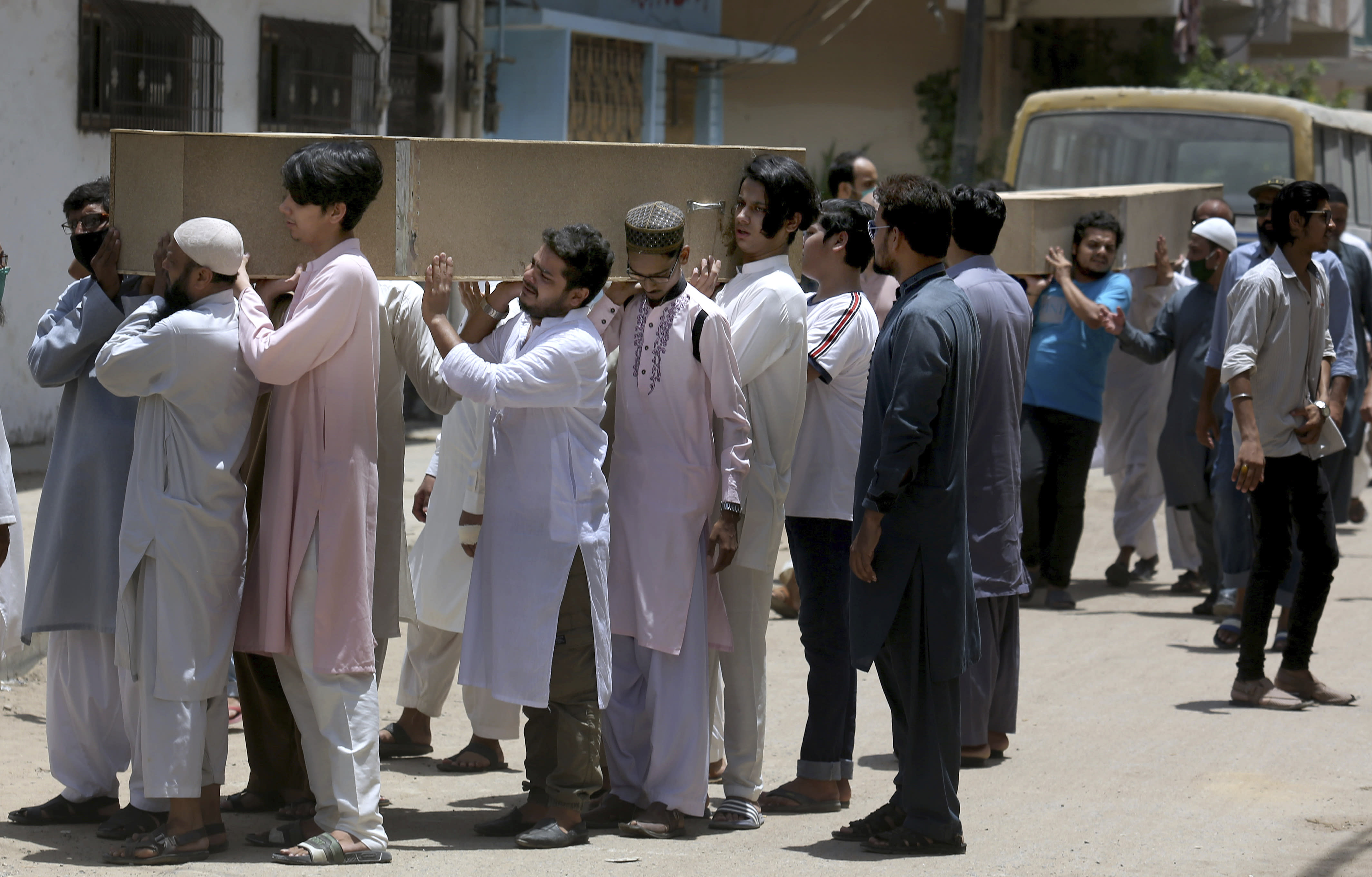 People carry the casket of the victims of Friday's plane crash for funeral prayers in Karachi, Pakistan, Saturday, May 23, 2020. An aviation official says a passenger plane belonging to state-run Pakistan International Airlines carrying passengers and crew has crashed near the southern port city of Karachi. (AP Photo/Fareed Khan)