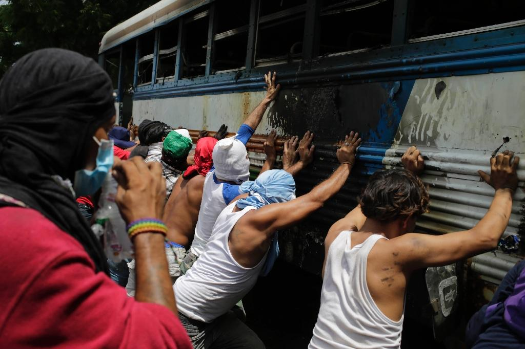 Demonstrators try to turn over a bus set alight during a day-long national strike in Nicaragua (AFP Photo/Inti OCON)