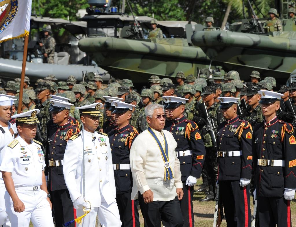 Philippine defense secretary Voltaire Gazmin (front R) inspects personnel during the navy's founding anniversary celebration at a naval station in Cavite city, west of Manila on May 25, 2015 (AFP Photo/Ted Aljibe)