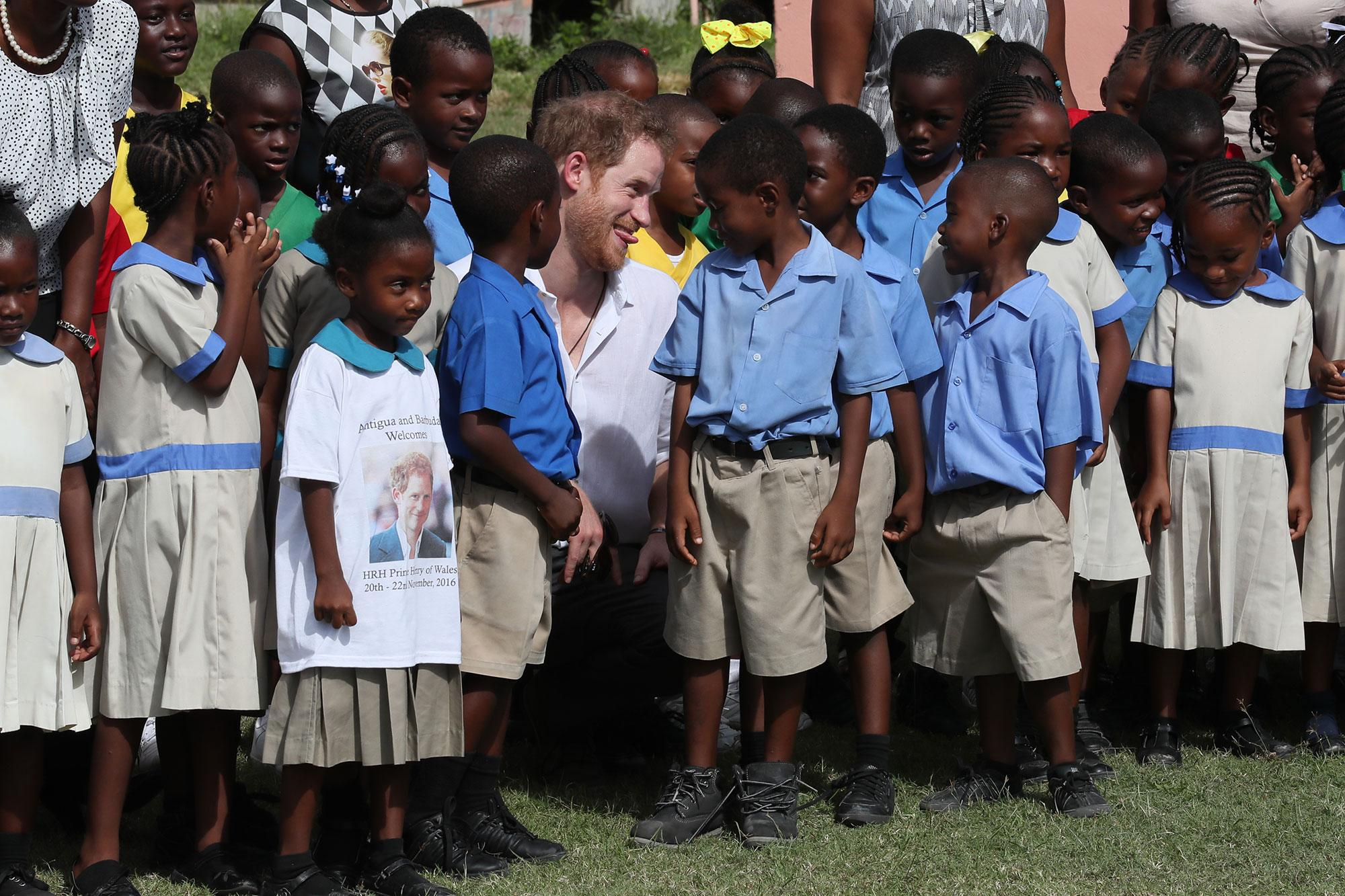 <p>Prince Harry meets school children at Holy Trinity Primary School and Nursery, as they prepare celebrations for the school's 93rd anniversary of their Founders' Day, during the third day of his tour of the Caribbean on November 22, 2016 in Barbuda, Antigua and Barbuda. (Chris Radburn – Pool/Getty Images) </p>