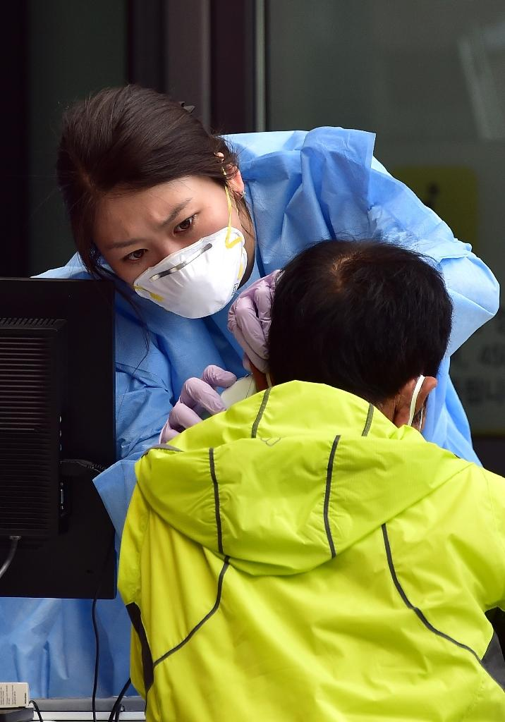 A South Korean medical worker takes a patient's body temperature at a special clinic where patients with respiratory issues can be treated in Seoul, on June 16, 2015 (AFP Photo/Jung Yeon-Je)