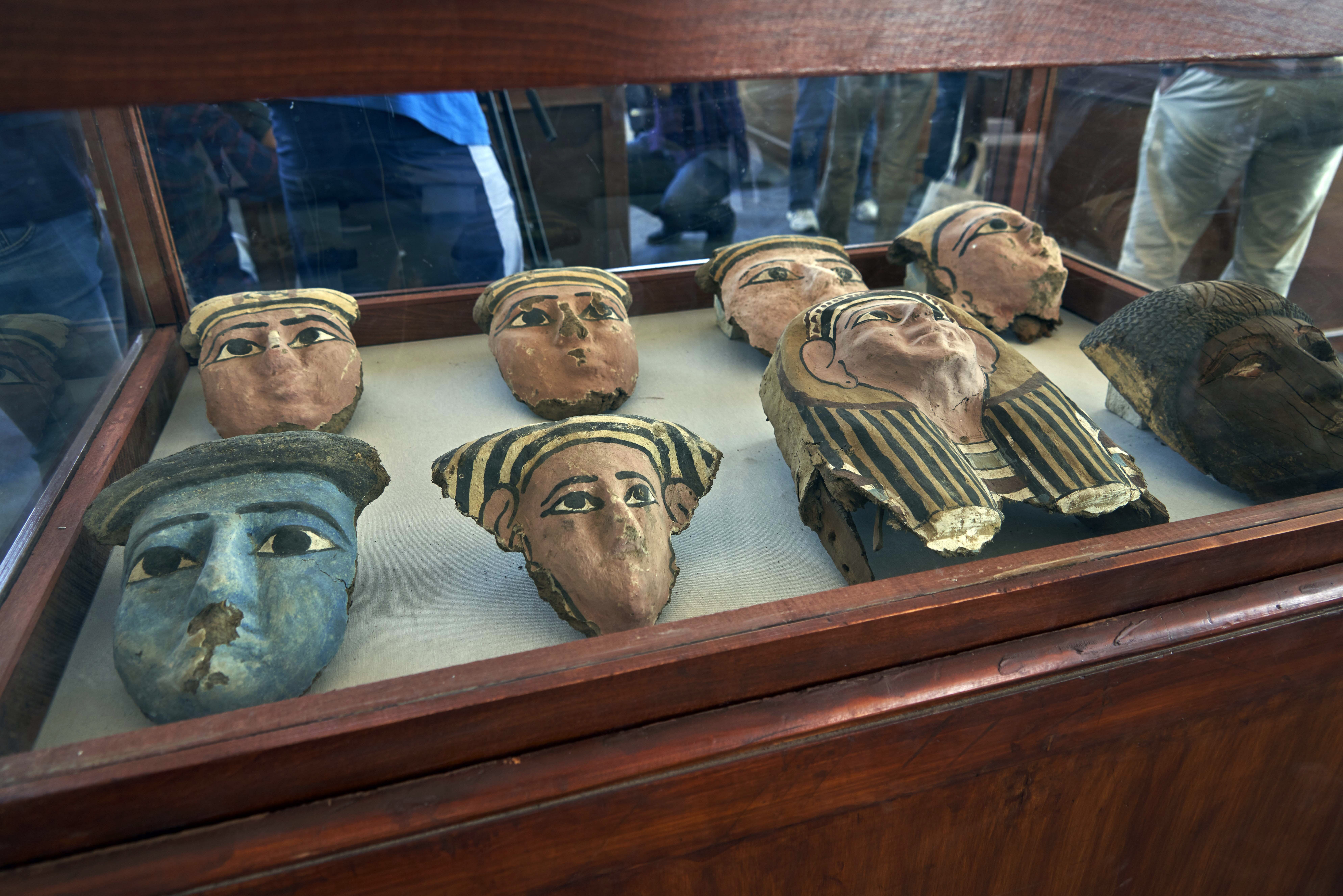 Wooden and clay mummies masks are displayed in Saqqara, south Giza, Egypt. Saturday, Nov. 23, 2019. Egypt's Ministry of Antiquities revealed details on recently discovered animal mummies, saying they include two lion cubs as well as several crocodiles, birds and cats. The new discovery was displayed at a makeshift exhibition at the famed Step Pyramid of Djoser in Saqqara, south of Cairo, near the mummies and other artifacts were found in a vast necropolis. (AP Photo/Hamada Elrasam)
