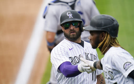 Colorado Rockies' Raimel Tapia, right, congratulates Kevin Pillar, left, after the pair scored on a single hit by Josh Fuentes off Los Angeles Dodgers starting pitcher Tony Gonsolin in the fourth inning of a baseball game Sunday, Sept. 20, 2020, in Denver. (AP Photo/David Zalubowski)