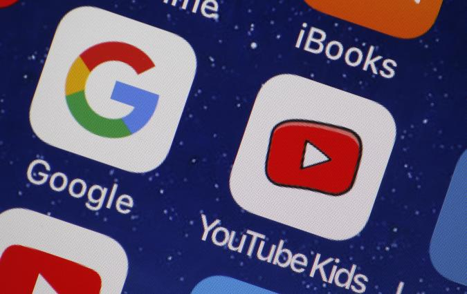 PARIS, FRANCE - APRIL 10:  In this photo illustration, the logo of the Google and You Tube Kids applications are displayed on the screen of an Apple iPhone on April 10, 2018 in Paris, France. Twenty-three US digital rights and child protection organizations have accused YouTube and its parent company Google of collecting personal data about children and using it to target advertisements, a complaint has been filed with the FTC, the US trade regulator.  (Photo by Chesnot/Getty Images)
