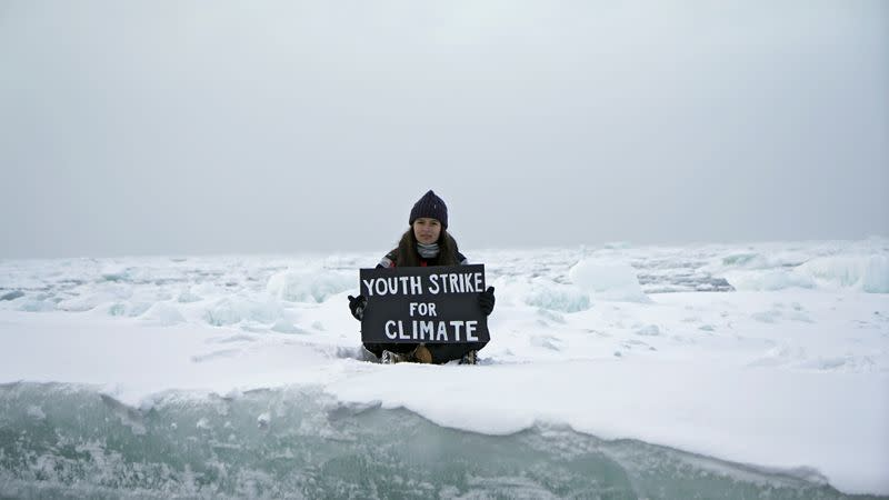 """Environmental activist and campaigner Mya-Rose Craig holds a cardboard sign reading """"youth strike for climate"""" in the middle of the Arctic Ocean"""