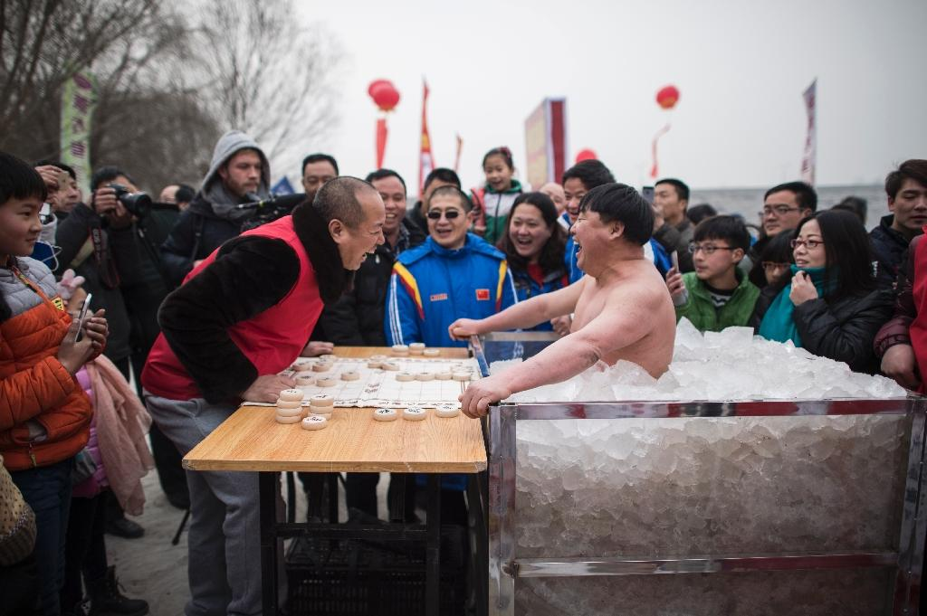 """Cui Deyi, known as """"Polar Bear,"""" plays mahjong while standing in a box filled with ice in Handan, in China's Hebei province on January 16, 2016 (AFP Photo/Fred Dufour)"""