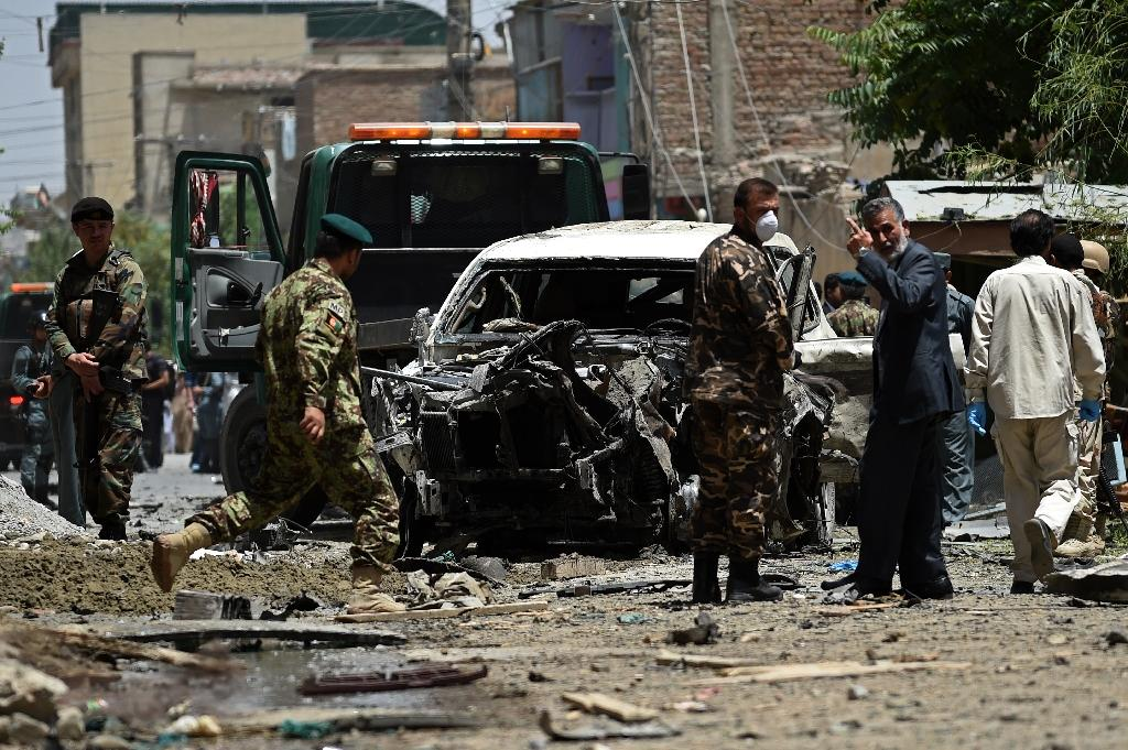 Security forces inspect a damaged vehicle at the site of a bomb blast that targeted NATO forces in Kabul on July 7, 2015 (AFP Photo/Wakil Kohsar)