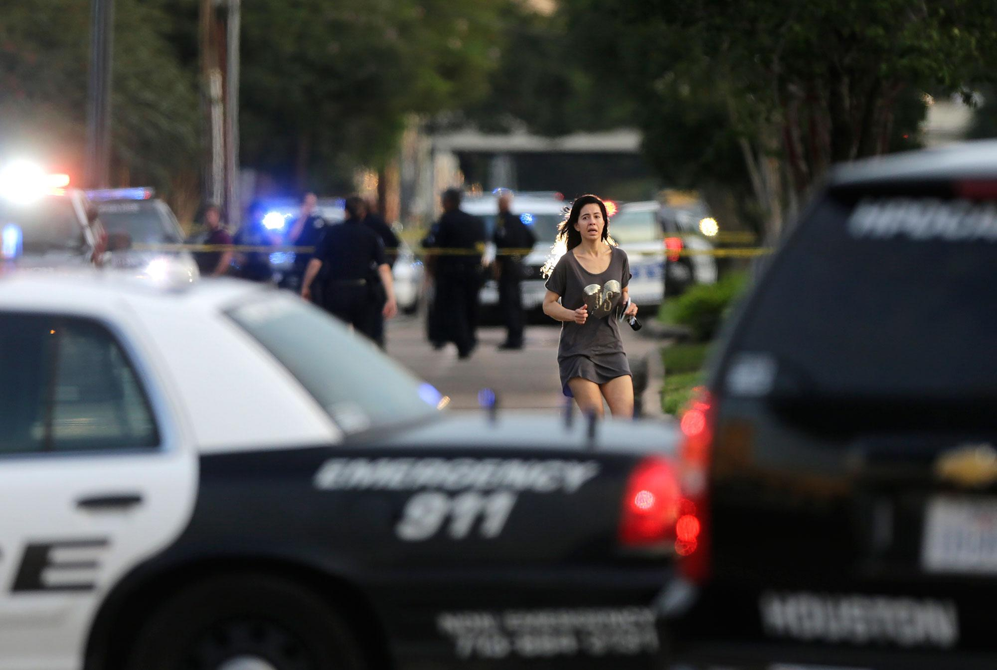 <p>Jennifer Molleda runs down Wesleyan Street in Houston to find her husband, Alan Wakim, who had two bullets whiz by his face after going through his windshield on the way to work along Wesleyan at Law Street in a shooting that left multiple people injured and the alleged shooter dead, Monday morning, Sept. 26, 2016. (Mark Mulligan/Houston Chronicle via AP) </p>