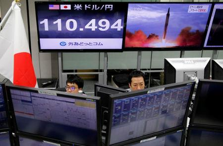 Employees of a foreign exchange trading company work in front of monitors showing TV news on North Korea's threat (R) and the Japanese yen's exchange rate against the U.S. dollar (L) in Tokyo, Japan, September 14, 2017. REUTERS/Toru Hanai