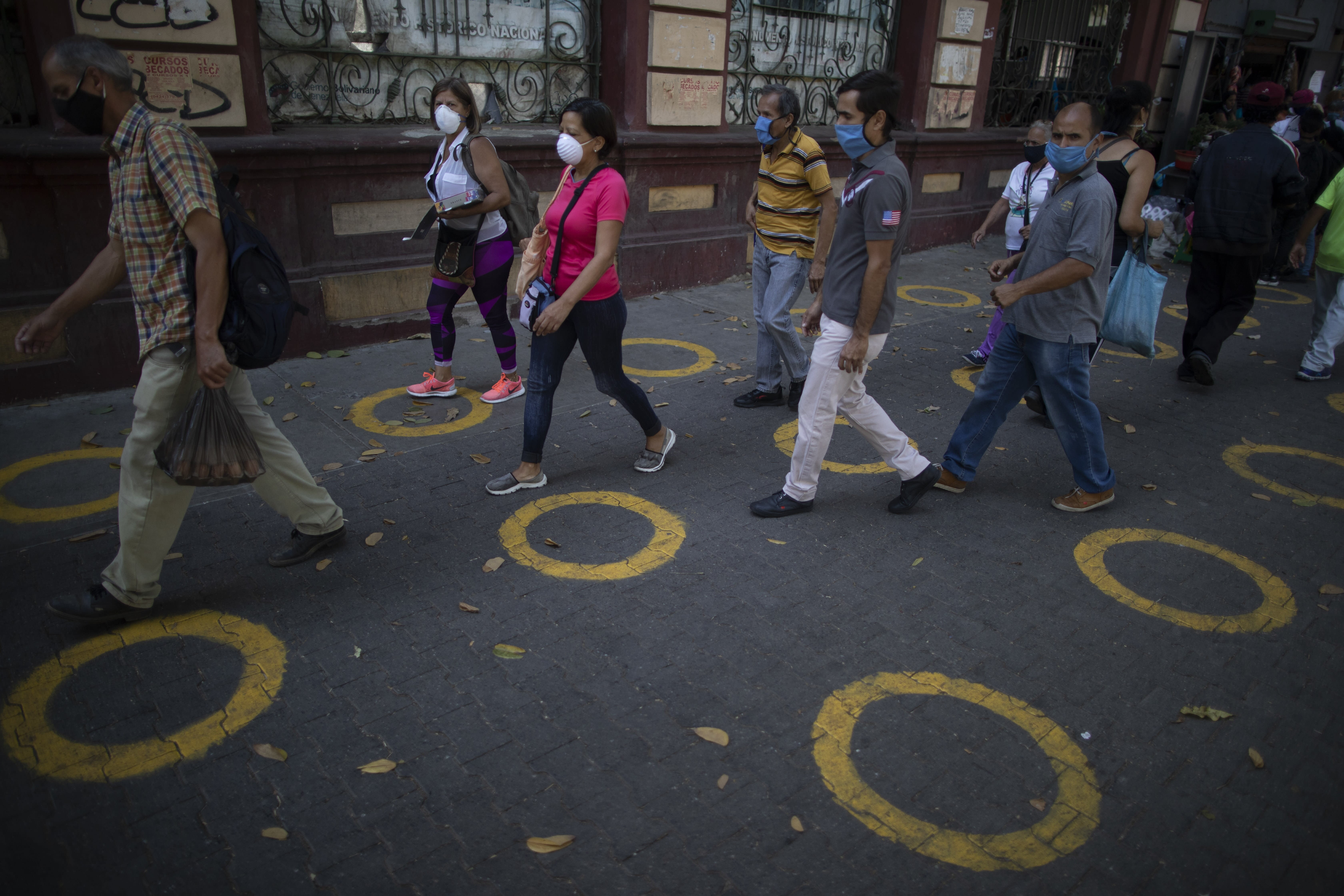 Yellow circles on a pavement serve as visual cues to help shoppers adhere to social distancing when lines form, as a precaution against the spread of the new coronavirus, near a popular market in Caracas, Venezuela, Saturday, May 23, 2020. (AP Photo/Ariana Cubillos)