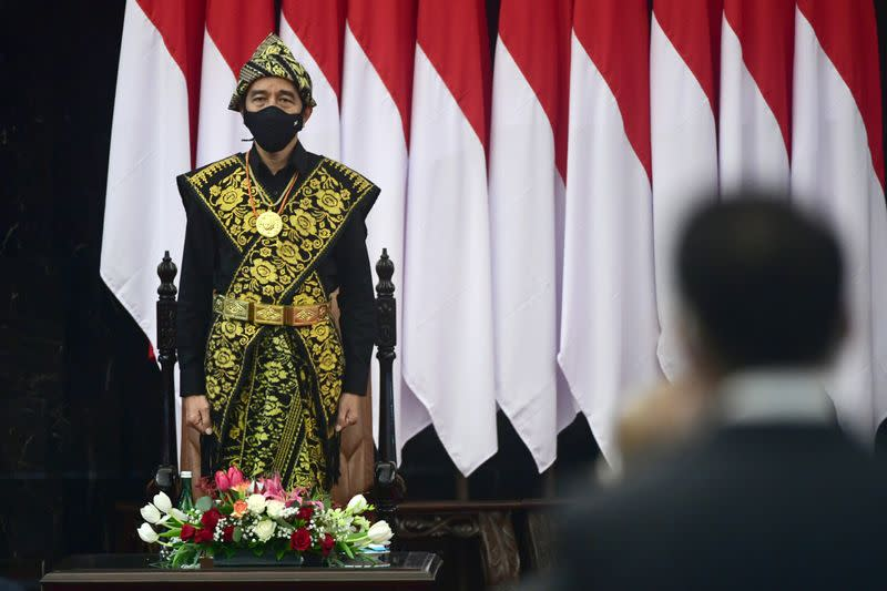 Indonesian President Joko Widodo dressed in a traditional Indonesian costume from Sabu, stands before delivering a speech ahead of the 75th Independence Day, at the parliament building in Jakarta