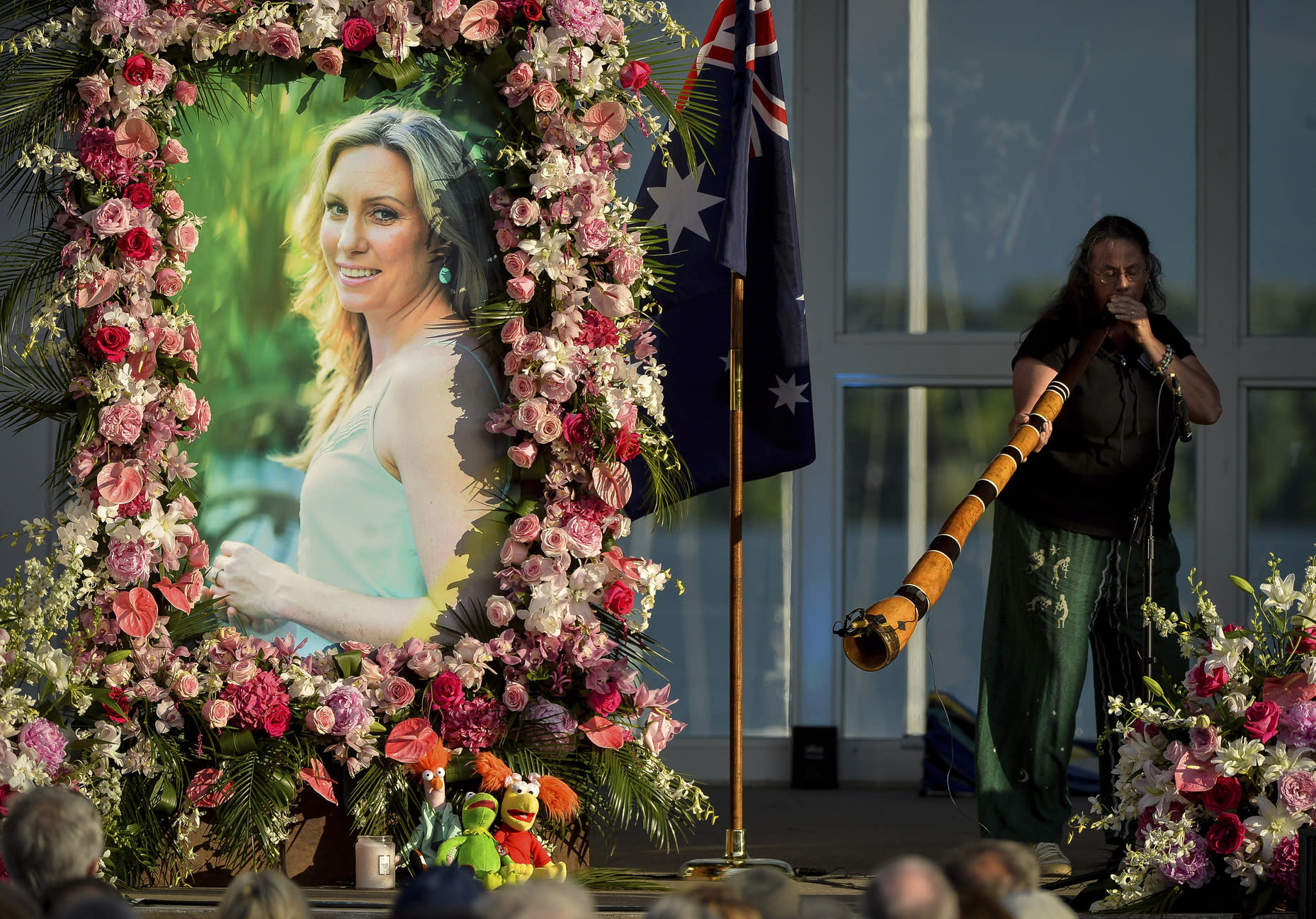 FILE - In this Aug. 11, 2017, file photo, Johanna Morrow plays the didgeridoo during a memorial service for Justine Ruszczyk Damond at Lake Harriet in Minneapolis. Jurors on Wednesday, April 10, 2019, heard the 911 calls Damond made to report a possible sexual assault before she was shot by a Minneapolis officer now on trial for murder in her death. (Aaron Lavinsky/Star Tribune via AP, File)
