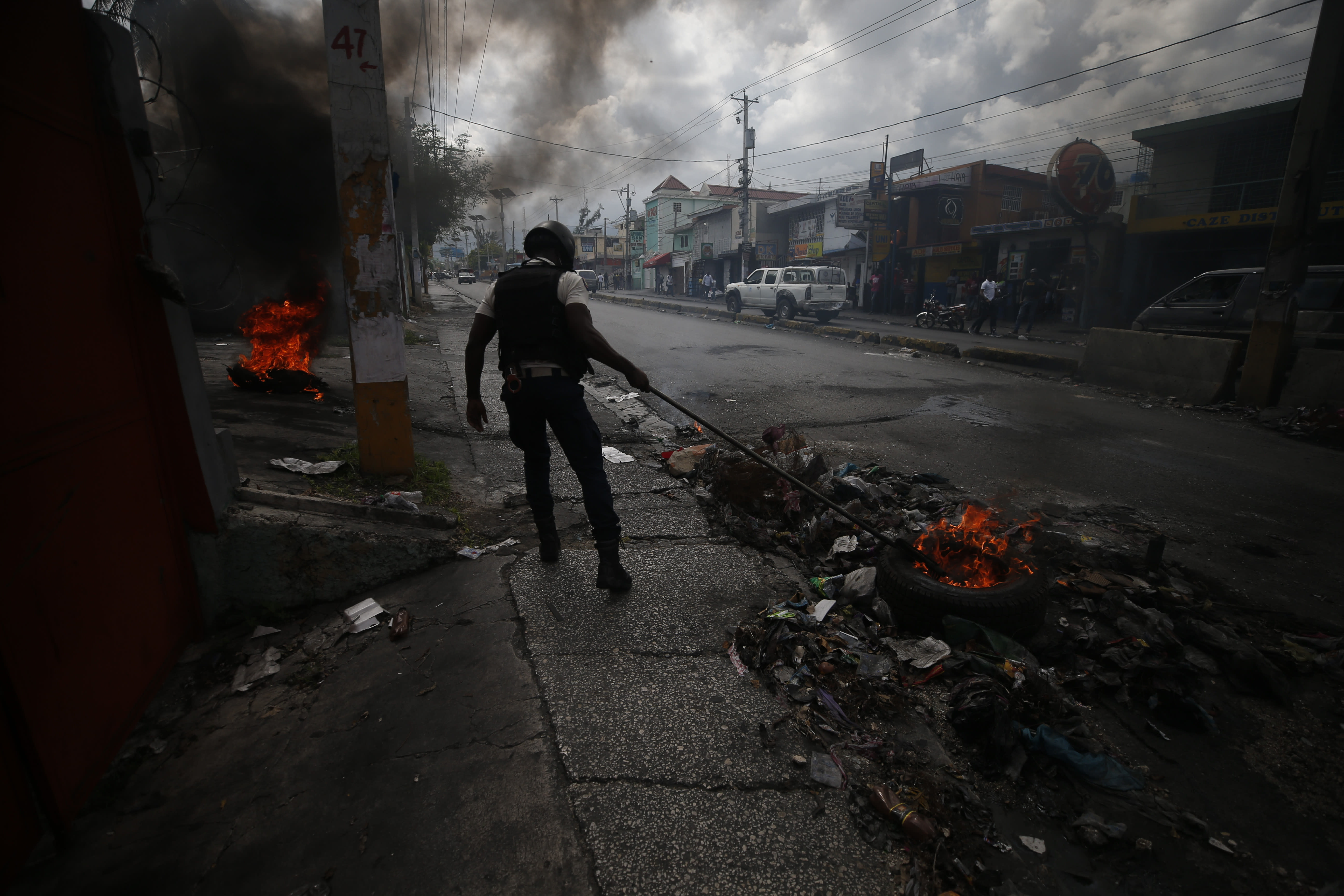 """A policeman uses a rake to drag burning tires out of the road as police break up a barricade in Port-au-Prince, Haiti, Wednesday, Oct. 2, 2019. A group of men was protesting at the intersection after commissioning a mural of opposition organizer Jose Mano Victorieux, known as """"Badou,"""" who they said was executed Saturday night by unknown assailants.(AP Photo/Rebecca Blackwell)"""
