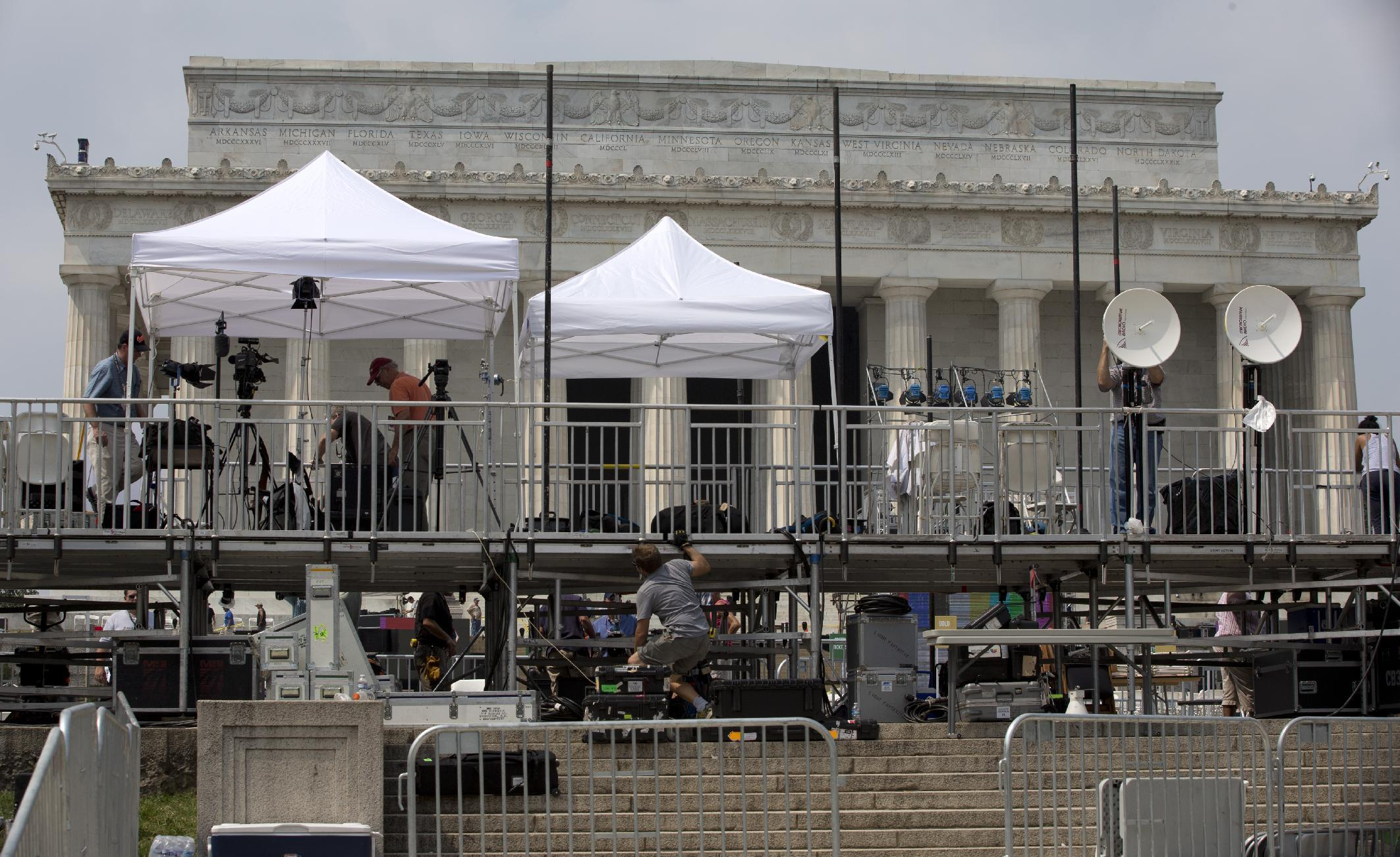 """Members of the media set up equipment in front of the Lincoln Memorial in Washington, Tuesday, Aug. 27, 2013, for the 50th anniversary of the March On Washington celebrations that will be held Wednesday, Aug, 28, 2013. Barack Obama, who will speak, was 2 years old and growing up in Hawaii when Martin Luther King Jr. delivered his """"I Have a Dream"""" speech from the steps of the Lincoln Memorial. Fifty years later, the nation's first black president will stand as the most high-profile example of the racial progress King espoused, delivering remarks at a nationwide commemoration of the 1963 demonstration for jobs, economic justice and racial equality. (AP Photo/Carolyn Kaster)"""