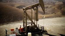 Oil bounces up off 10-month lows; crude glut still weighs