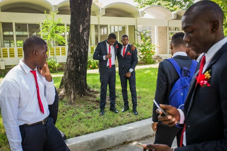 Seniors at Saint-Louis de Gonzague school in Port-au-Prince, Haiti, gather after their graduation photo on August 4, 2020; with Haitian schools set to reopen nationwide, a huge opportunity gap separates them