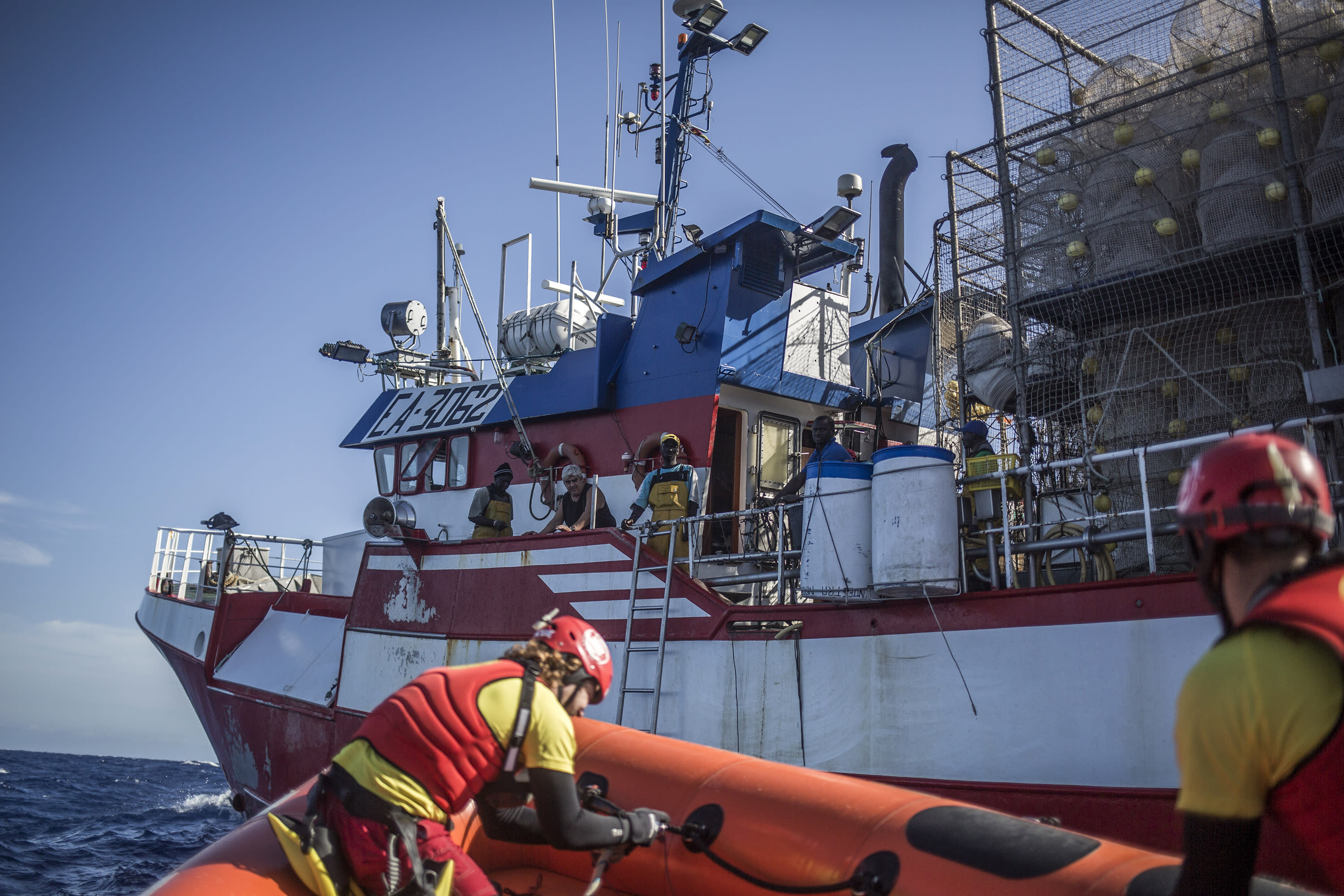 In this photo taken on Saturday, Nov. 24, 2018 photo, Members of Spanish NGO Proactiva Open Arms approach Nuestra Madre de Loreto, a Spanish fishing vessel that rescued twelve migrants and refugees two days ago about 78 miles north off Libyan shore. (AP Photo/Javier Fergo)