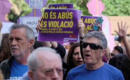 """People shout slogans during a protest outside the City of Justice, after a Spanish court on Thursday sentenced five men accused of the group rape of an 18-year-old woman at the 2016 San Fermin bull-running festival each to nine years in prison for the lesser charge of sexual abuse, in Valencia, Spain April 27, 2018. The sign read: """"It is not abuse, it is rape"""" and """"Sister, I do believe you; there is enough of patriarchal justice"""". REUTERS/Heino Kalis"""