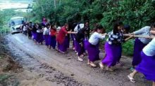 Indian schoolgirls form human chain to pull bus out of mud