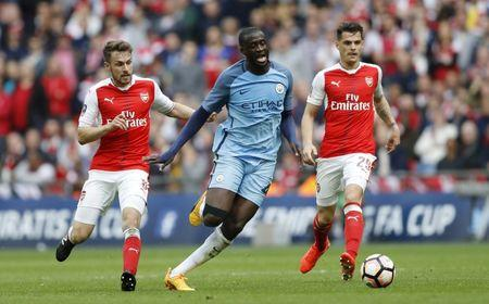 Manchester City's Yaya Toure in action with Arsenal's Aaron Ramsey and Granit Xhaka