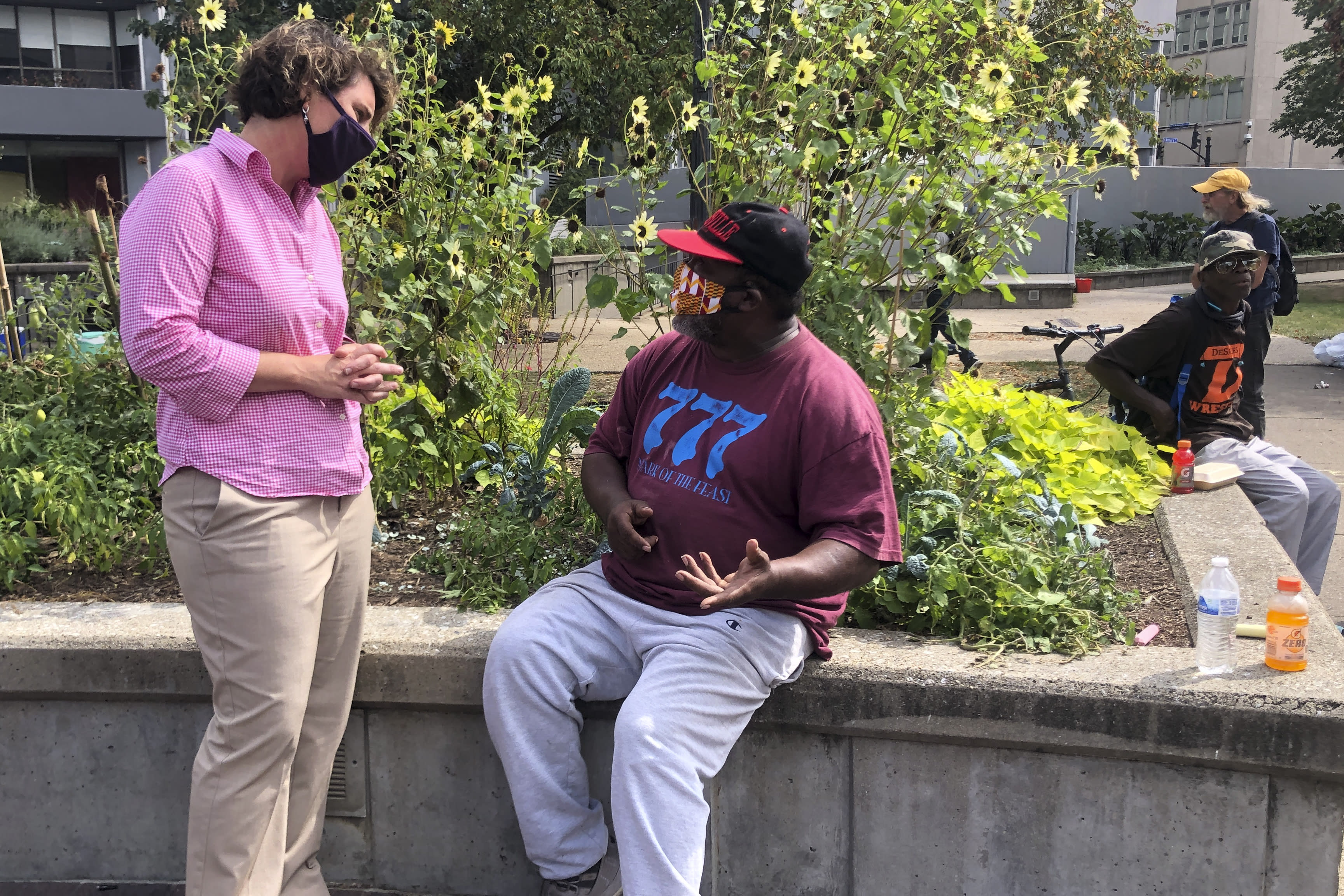 """Kentucky U.S. Senate candidate Democrat Amy McGrath, speaks to a man in Jefferson Square, Thursday, Sept. 24, 2020, in Louisville, Ky. McGrath called for fundamental change to combat """"systemic racism"""" as the Senate candidate met Thursday with some of the Kentucky protesters seething over a grand jury's decision not to charge officers for killing Breonna Taylor. (AP Photo/Claire Galofaro)"""