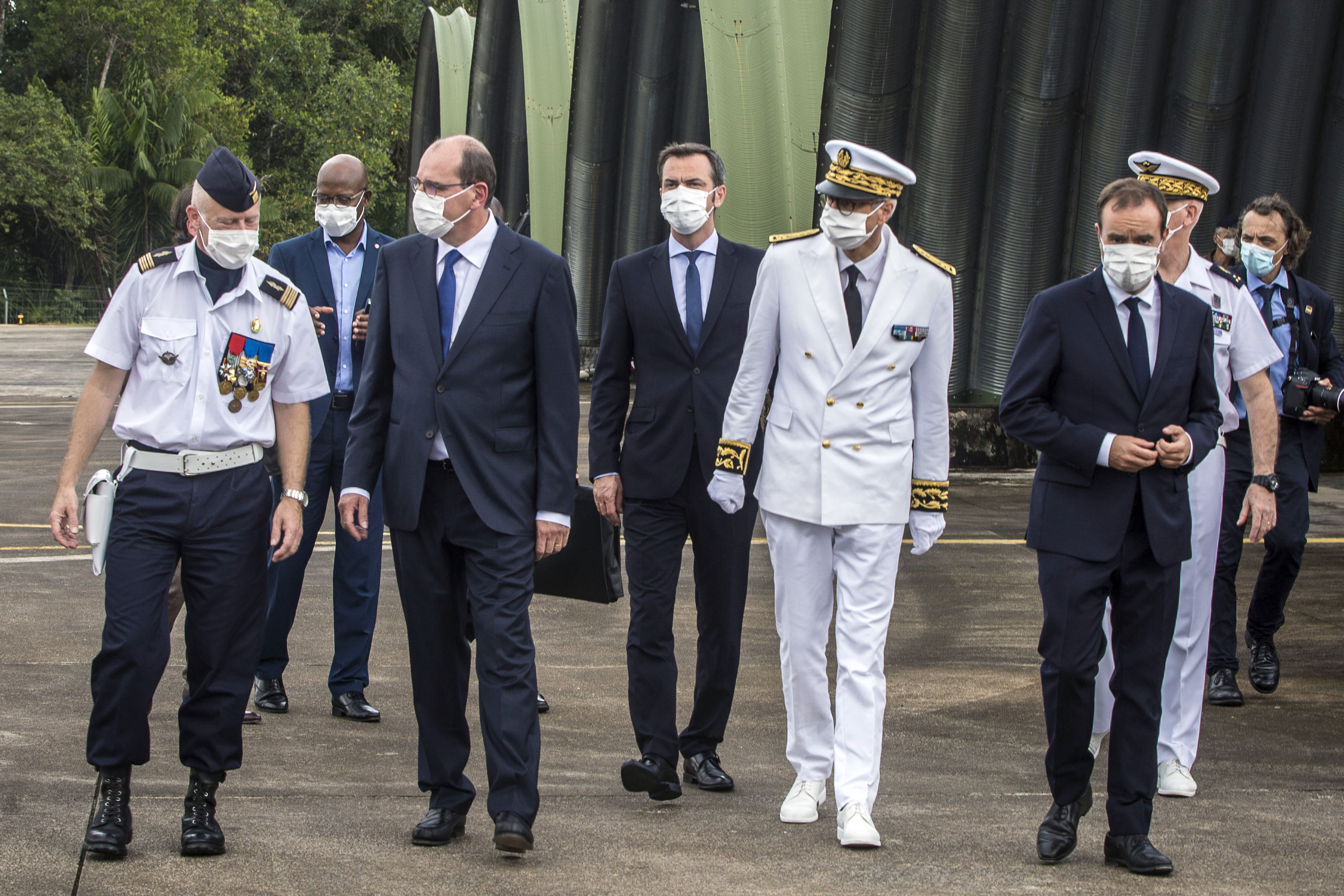 France's Prime Minister Jean Castex, center left, arrives with French Overseas Minister Sebastien Lecornu, right, and France's Health Minister, Olivier Veran, center, at the Matoury Air Base 367, near Cayenne, French Guiana, Sunday, July 12, 2020. As virus numbers soar in French Guiana, France's new prime minister traveled Sunday to the South American territory and promised not to ignore its suffering. (AP Photo/Pierre-Olivier Jay)