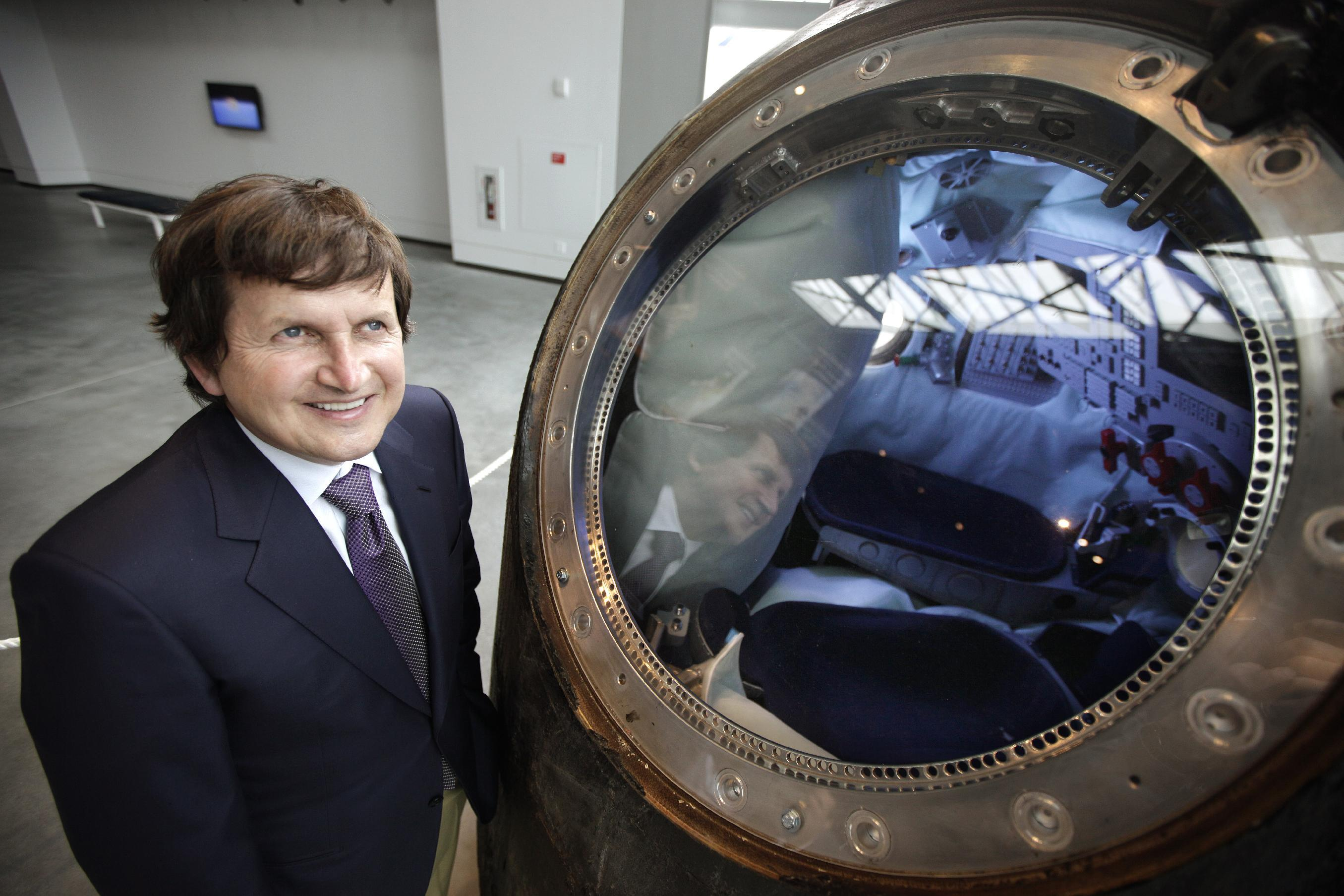 In this March 27, 2012, photo, Charles Simonyi, the only civilian to visit the International Space Station twice, poses for a photo next to the Soyuz TMA-14 descent module that took him to the International Space Station on his second trip into space, at the Seattle's Museum of Flight's new space gallery, which is named after him. The Microsoft billionaire is still obsessed with space, but has no plans to take a third trip, instead he's focused on publishing a physics book written by his father and continuing to work with the museum. (AP Photo/Ted S. Warren)