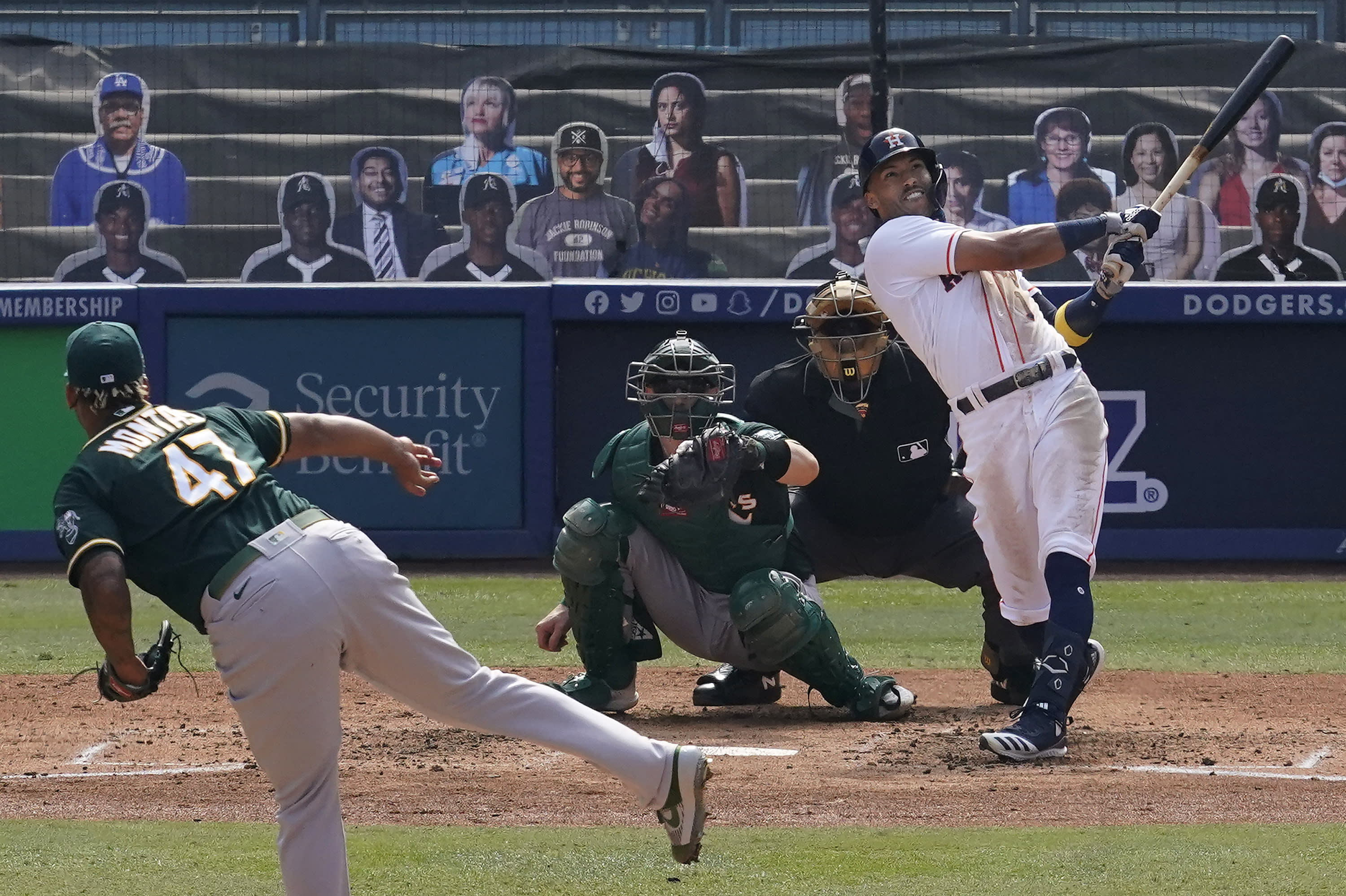 Houston Astros' Carlos Correa, right, hits a three-run home run off of Oakland Athletics pitcher Frankie Montas, left, during the fourth inning of Game 4 of a baseball American League Division Series in Los Angeles, Thursday, Oct. 8, 2020. (AP Photo/Marcio Jose Sanchez)