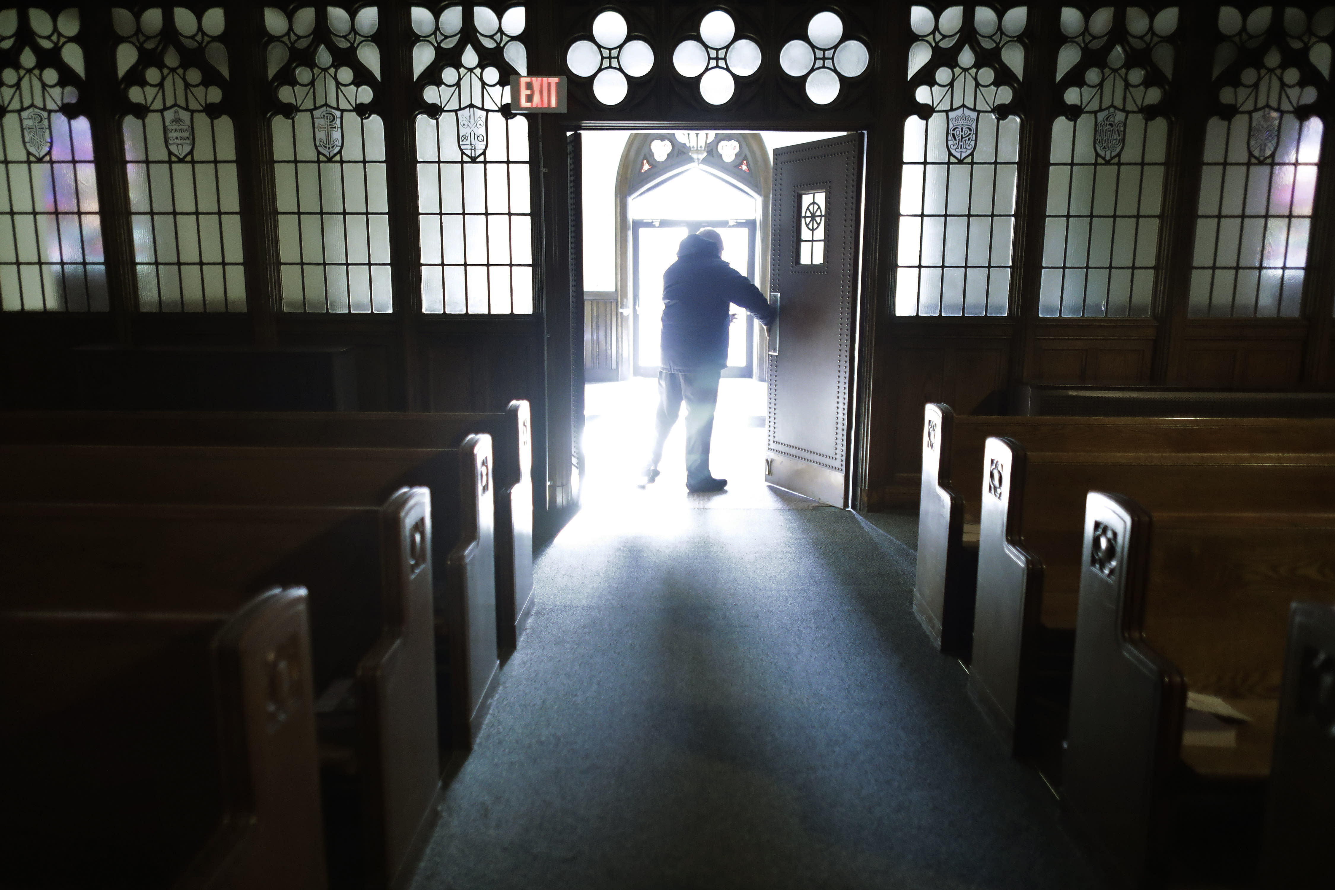 In this Saturday, Nov. 9, 2019 photo, Rev. Mark Stelzer, administrator of St. Jerome's Parish, in Holyoke, Mass., opens doors to the Catholic church before offering Mass. Stelzer, also a professor and chaplain at College of Our Lady of the Elms, in Chicopee, Mass., lives alone in the rectory at St. Jerome's while serving as spiritual leader to the 500 families in the Catholic parish. (AP Photo/Steven Senne)