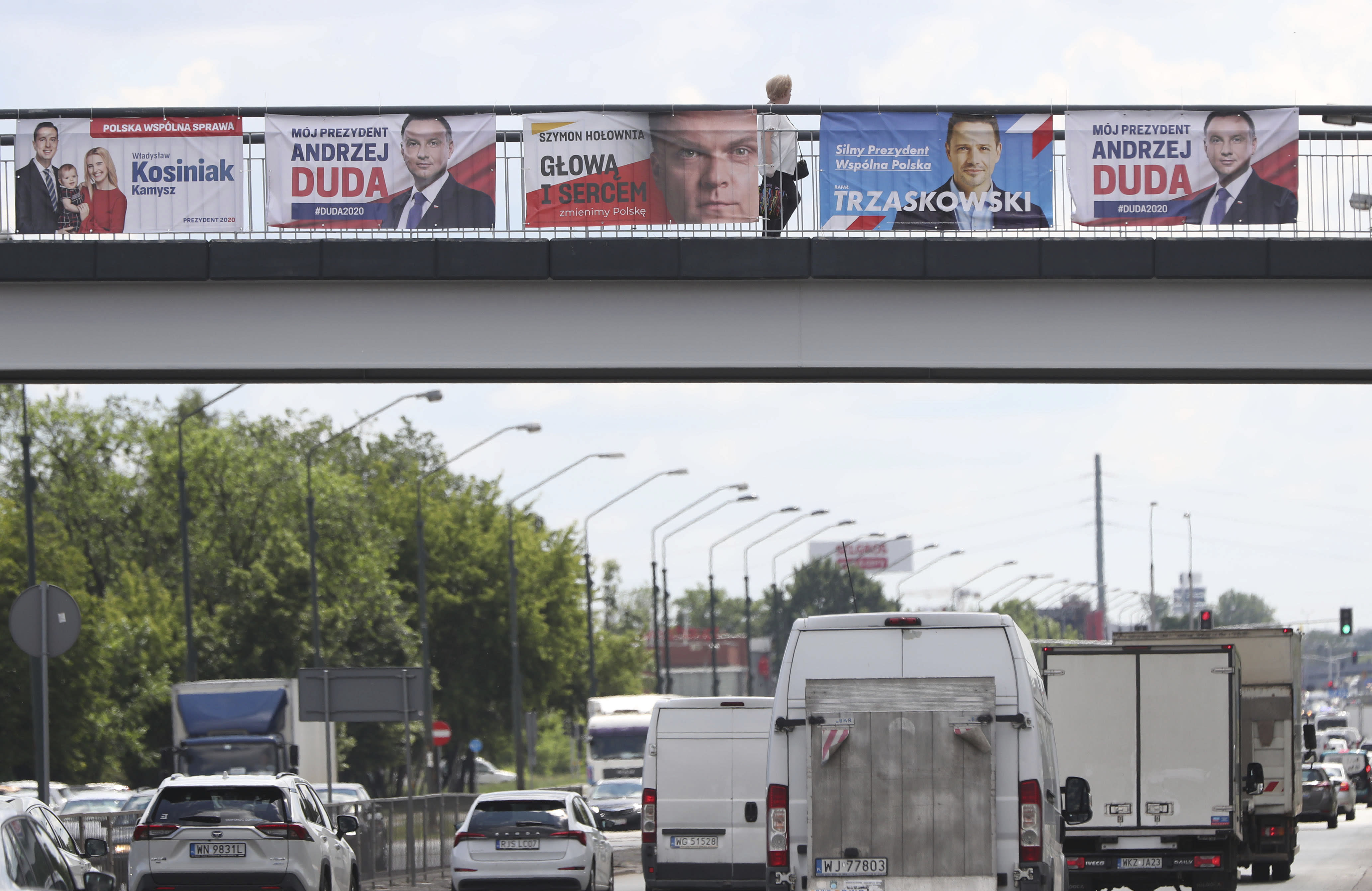 Electoral posters for Poland's conservative President Andrzej Duda and his three main challengers in Sunday's presidential election placed above a major thoroughfare n Warsaw, Poland, Tuesday, June 23, 2020.Centrist Warsaw Mayor Rafal Trzaskowski is considered Duda's main challenger who could face the incumbent in a runoff.(AP Photo/Czarek Sokolowski)