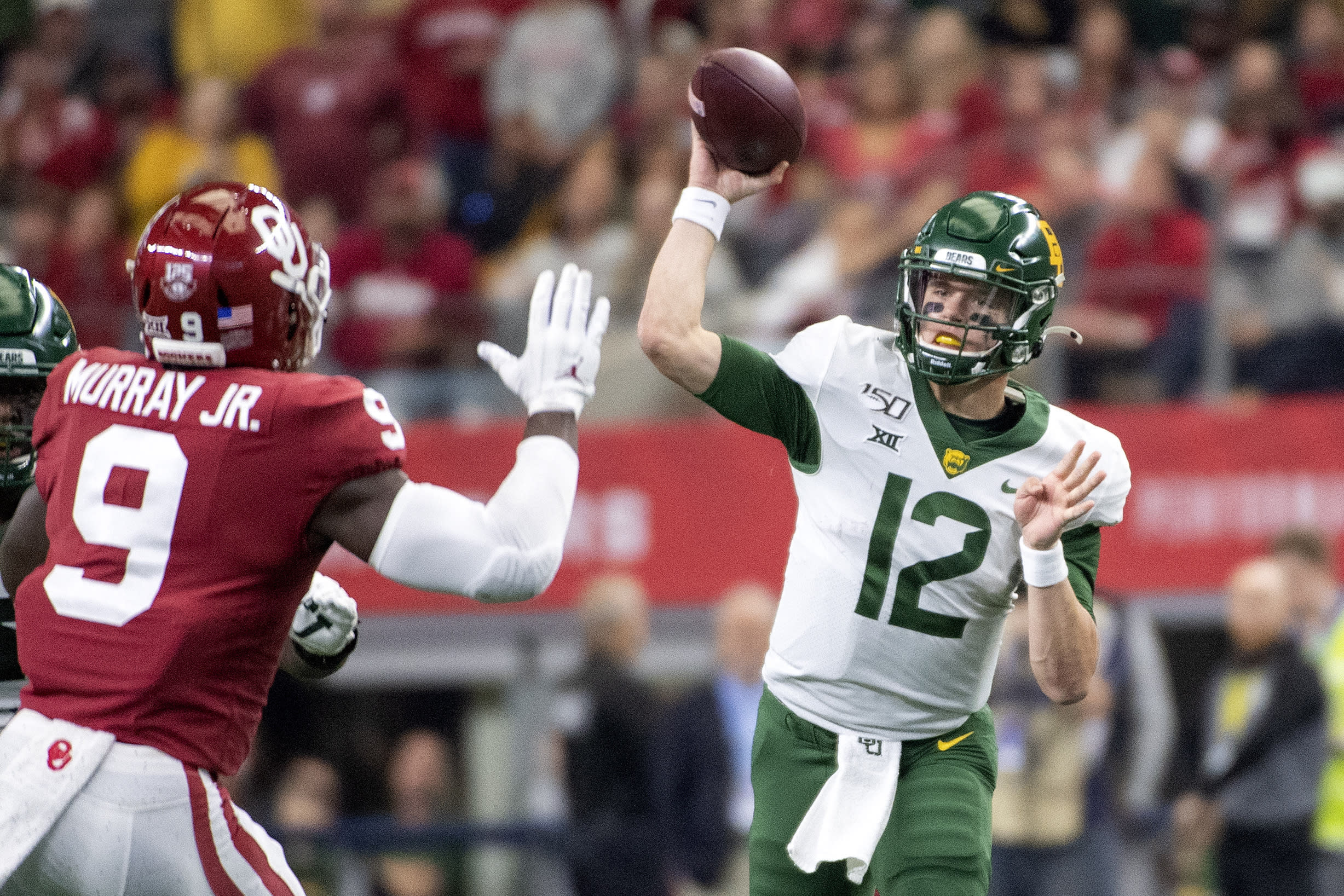 File-Baylor quarterback Charlie Brewer (12) throws past the defense of Oklahoma linebacker Kenneth Murray (9) during the first half of an NCAA college football game for the Big 12 Conference championship, Saturday, Dec. 7, 2019, in Arlington, Texas. Brewer never spent a lot of time thinking about how beat up he was at the end of last season after a tough finish for the Bears. But he just might slide a little more in his fourth season as Baylor starter, when the Big 12 runner-up Bears hope to get a step farther with a new coach coming off a national championship. (AP Photo/Jeffrey McWhorter, File)