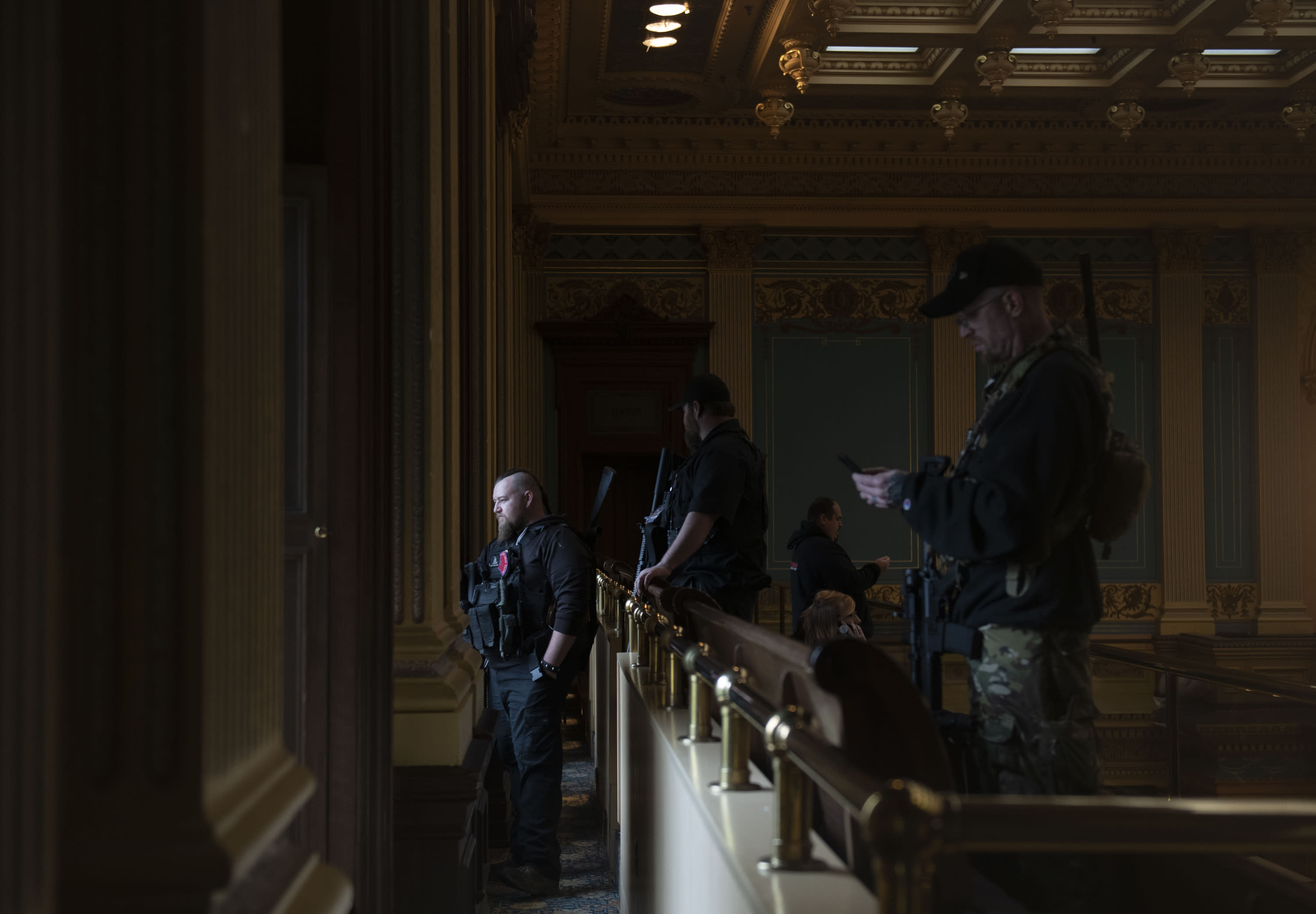 In this April 30, 2020, photo, members of a militia group watch the protest outside while waiting for the Michigan Senate to vote at the Capitol in Lansing, Mich. Gun-carrying protesters have been a common sight at some demonstrations calling for coronavirus-related restrictions to be lifted. But an armed militia's involvement in an angry protest in the Michigan statehouse Thursday marked an escalation that drew condemnation and shone a spotlight on the practice of bringing weapons to protest. (Nicole Hester/MLive.com/Ann Arbor News via AP)