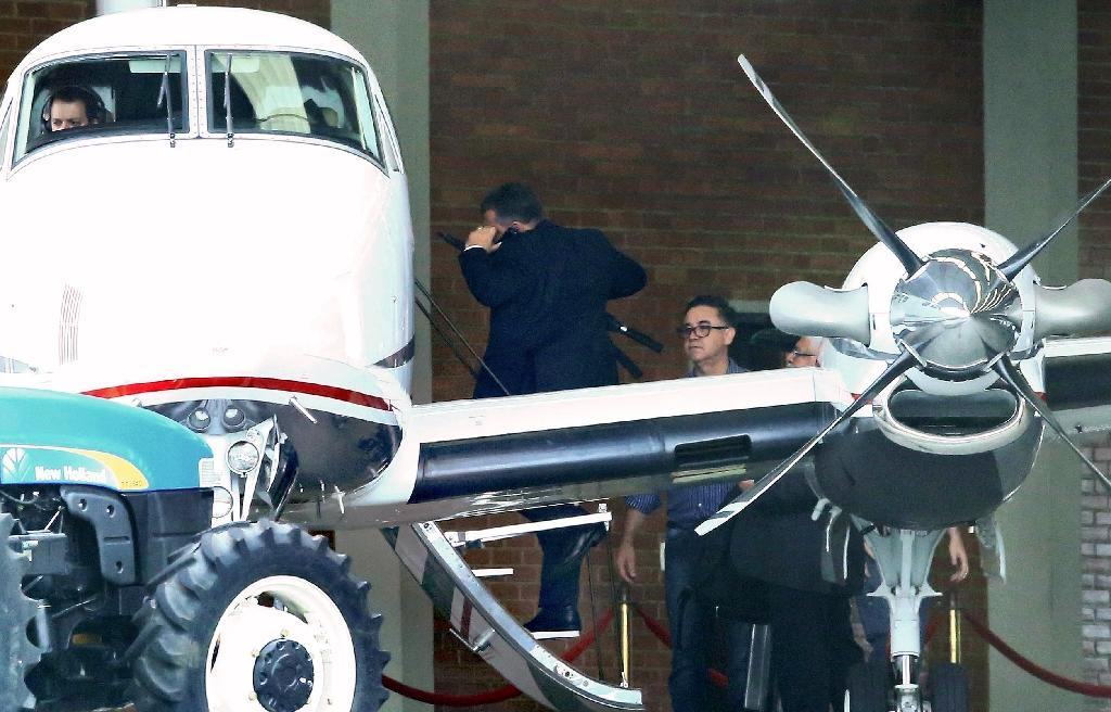 Marcelo Odebrecht (out of frame), gets onto a light aircraft with his lawyers at Bacacheri airport in the Brazilian southern city of Curitiba, after being released from prison for house arrest on December 19, 2017 (AFP Photo/Heuler Andrey)