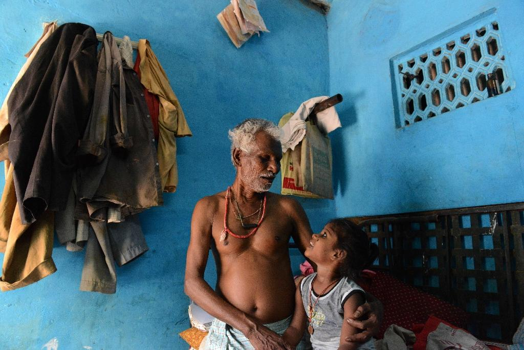 Sixty four-year-old Indian asbestosis sufferer Chinnapan Chinnakannu (L) sits with his granddaughter at his residence in the village of Kaligam, on the outskirts of Ahmedabad, May 7, 2015 (AFP Photo/Sam Panthaky)