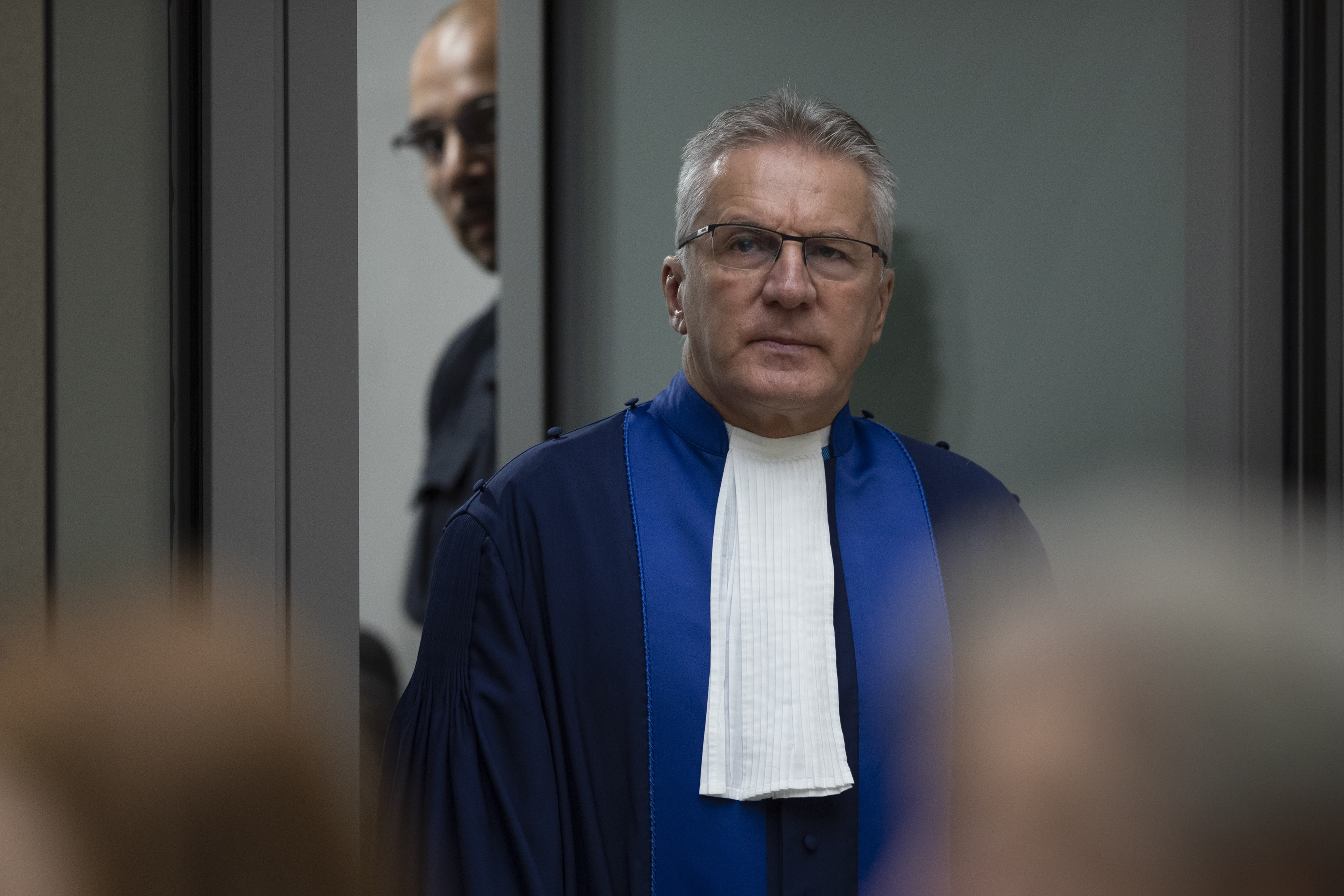 Presiding ICC judge Robert Fremr enters the courtroom to read the sentence for Congolese militia commander Bosco Ntaganda at the International Criminal Court in The Hague, Netherlands, Thursday, Nov. 7, 2019. The ICC delivered the sentence on Ntaganda, accused of overseeing the slaughter of civilians by his soldiers in the Democratic Republic of Congo in 2002 and 2003. (AP Photo/Peter Dejong, Pool)