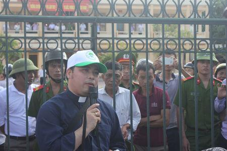 Catholic Priest Anthony Dang Huu Nam talks with Vietnamese fishermen who wait outside the people's court as they prepare to sue Formosa Ha Tinh Steel, a subsidiary of Taiwan's Formosa Plastics, over an accident at one of its steel plant which caused massive fish deaths along a 200-km (120-mile) stretch of coastline, in Vietnam's central province of Ha Tinh, September 26, 2016. Handout via