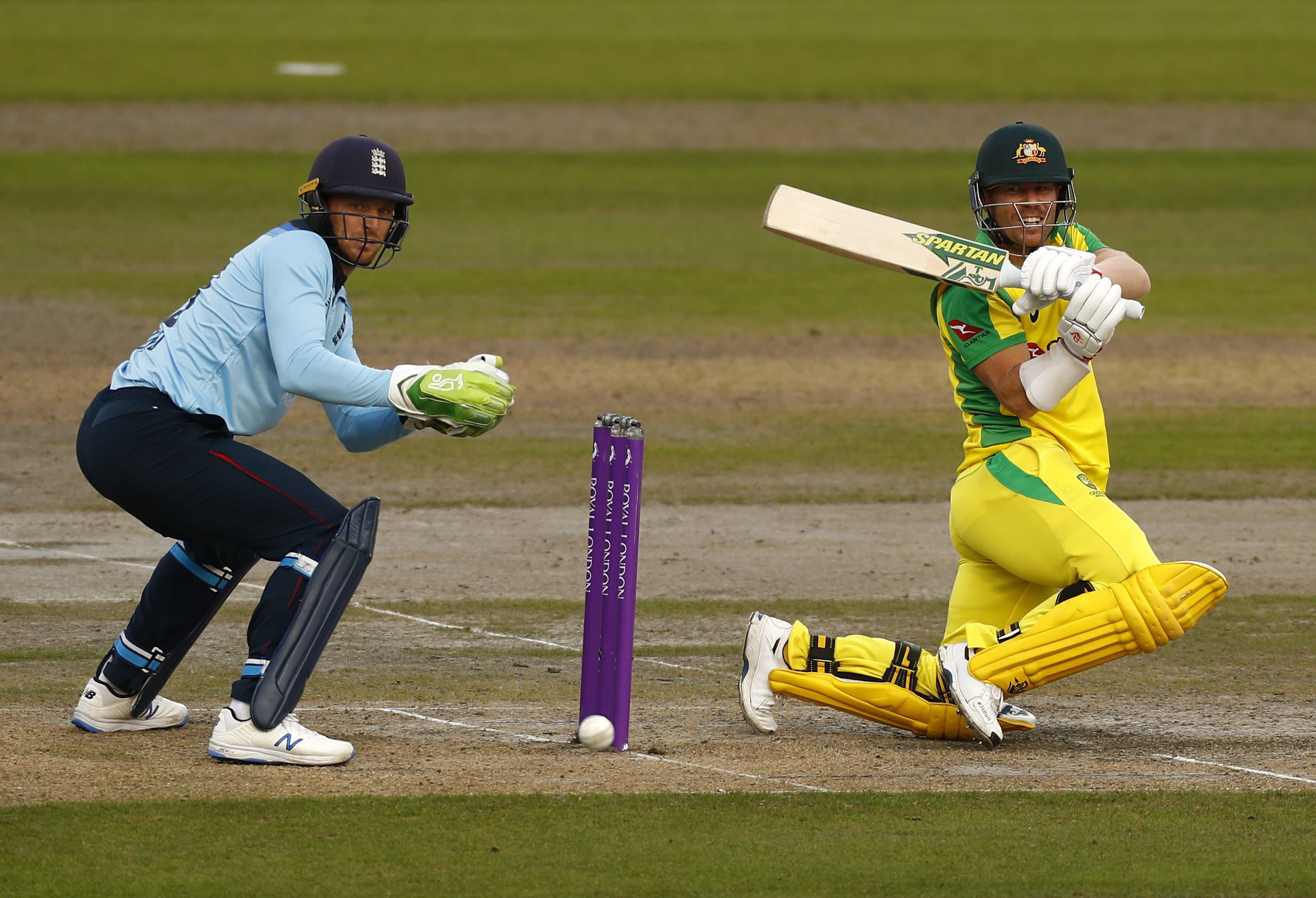 Australia's David Warner, right, plays a shot during the third ODI cricket match between England and Australia, at Old Trafford in Manchester, England, Wednesday, Sept. 16, 2020. (Jason Cairnduff/Pool via AP)