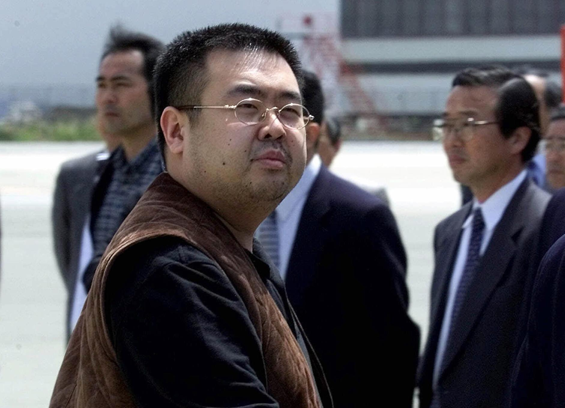 FILE - In this May 4, 2001, file photo, a man believed to be Kim Jong Nam, the eldest son of then North Korean leader Kim Jong Il, looks at a battery of photographers as he exits a police van to board a plane to Beijing at Narita international airport in Narita, northeast of Tokyo. Kim was assassinated at an airport in Kuala Lumpur, telling medical workers before he died that he had been attacked with a chemical spray a Malaysian official said Tuesday. (AP Photo/Shizuo Kambayashi, File)