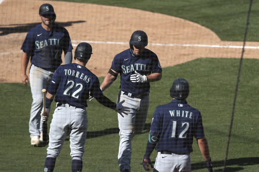 Seattle Mariners' Kyle Seager, center, celebrates with Luis Torrens (22) after hitting a two-run home run against the Oakland Athletics during the eighth inning of the first baseball game of a doubleheader in Oakland, Calif., Saturday, Sept. 26, 2020. (AP Photo/Jed Jacobsohn)