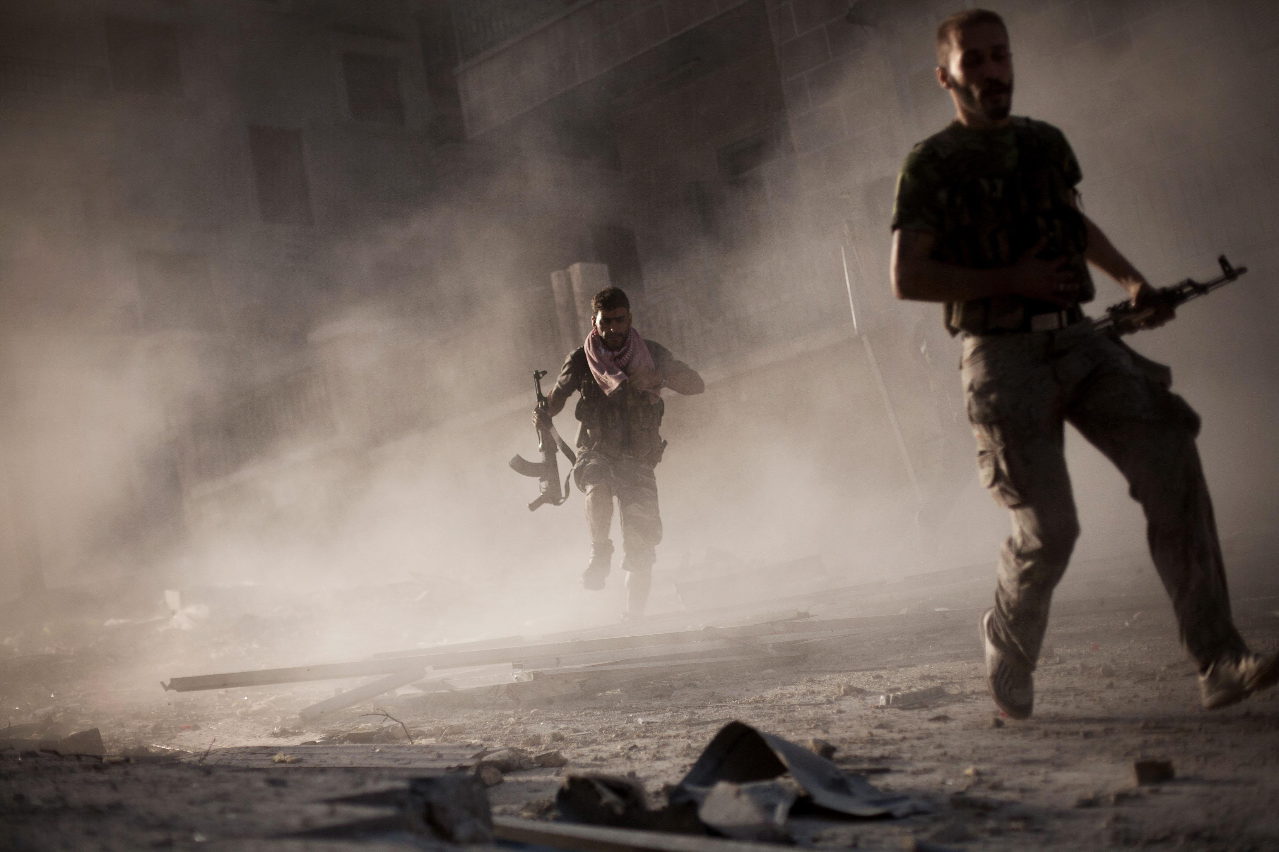 In this Friday, Sept 7, 2012 photo, Free Syrian Army fighters run after attacking a Syrian Army tank during fighting in the Izaa district in Aleppo, Syria. On Friday, U.S. Senators John McCain, Joe Lieberman and Lindsay Graham, who have toured the volatile Middle East in recent days, urged Washington to help arm Syria's rebels with weapons and create a safe zone inside the country for a transition government. (AP Photo/ Manu Brabo)