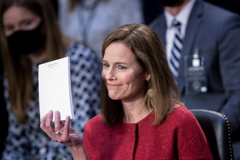 Amy Coney Barrett holds up a blank notepad after being asked what documents she had on her desk during her US Senate confirmation hearing to the Supreme Court