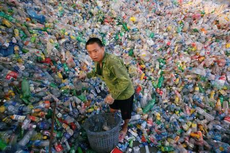 FILE PHOTO: A Vietnamese man works recycling plastic bottles at Xa Cau village outside Hanoi