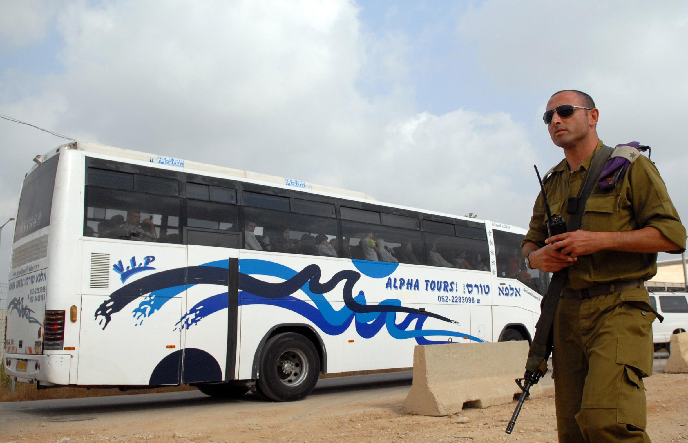 An Israeli army officer looks over a bus transporting Palestinians into Gaza Strip 29 July 2007 through the Erez crossing in Israel