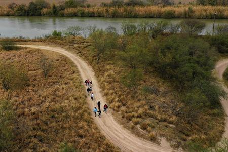 Migrant families seeking asylum walk down a dirt road after illegally crossing into the U.S. from Mexico in Penitas, Texas