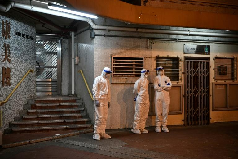 Medical personnel stand outside the apartment block in Hong Kong's Tsing Yi district (AFP Photo/Anthony WALLACE)