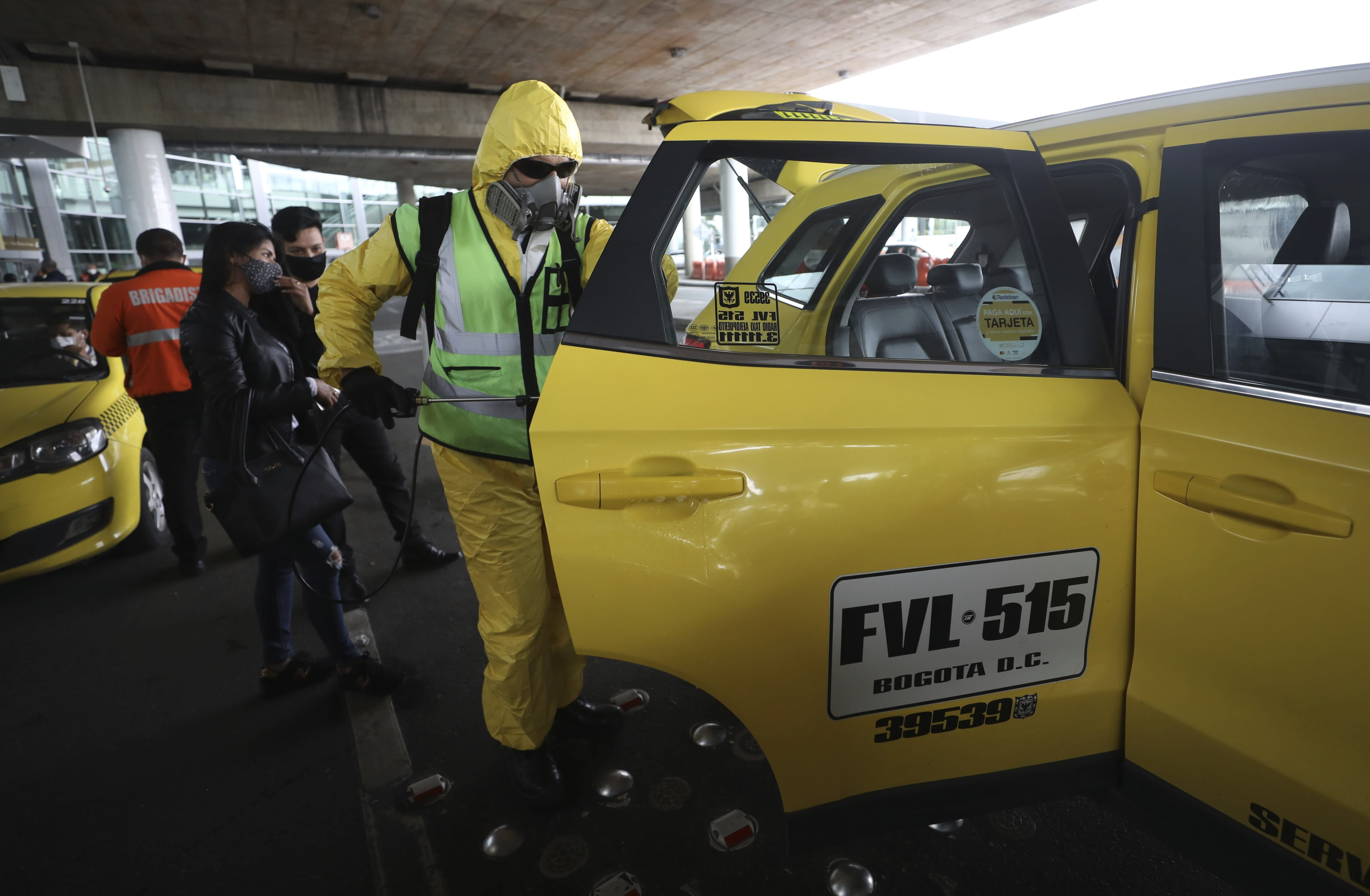 A worker disinfects a taxi for travelers arriving to El Dorado airport in Bogota, Colombia, Tuesday, Sept. 1, 2020. Airports, land transport, restaurants, and gyms are reopening in most of Colombia this week, as the South American nation attempts to reignite its economy following months of restrictions related to the coronavirus pandemic. (AP Photo/Fernando Vergara)