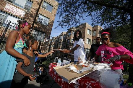 "Mothers Against Senseless Killings (MASK) founder Tamar Manasseh (R) and Eric ""Loco"" Gilbert (3rd R) serve food to residents in the Englewood neighborhood of Chicago, Illinois, United States, August 4, 2015. REUTERS/Jim Young"