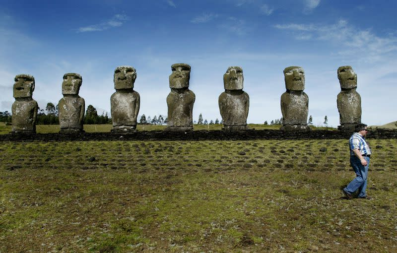 FILE PHOTO: TOURIST WALKS NEXT TO THE MOAI STATUES IN EASTER ISLAND.